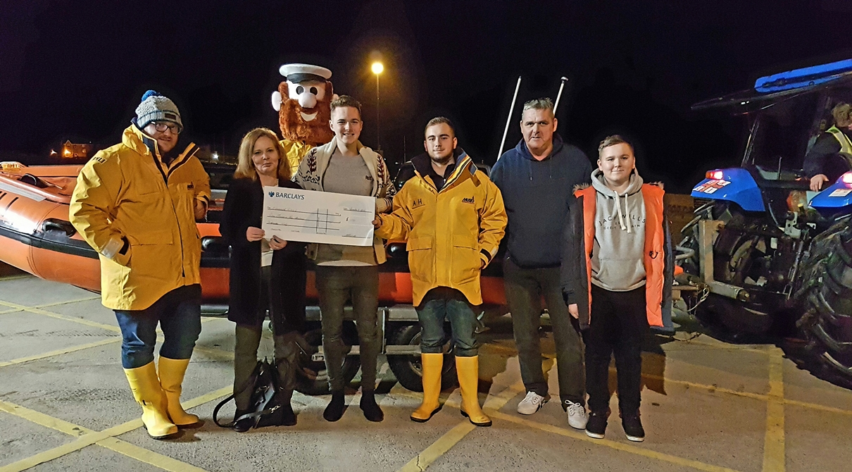 Barmouth RNLI volunteer crew members Anthony Schorah, Alex Hill and RNLI mascot Stormy Stan receiving the cheque from the Bowater family.