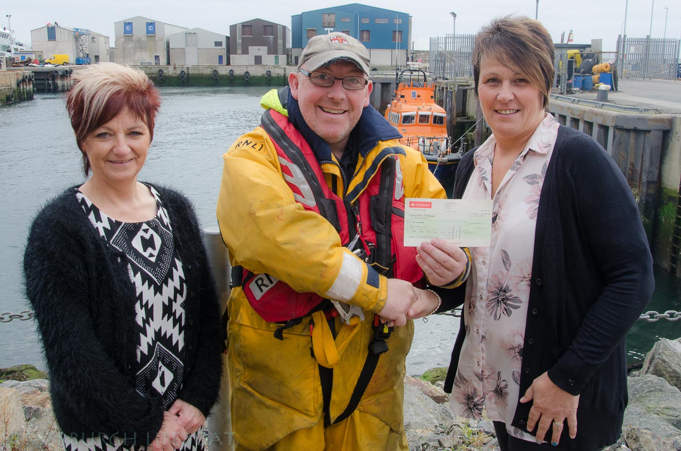 Moira and Denise present Coxswain Vic with Cheque from Wedding Exhibition with Fraserburgh Lifeboat in the background.