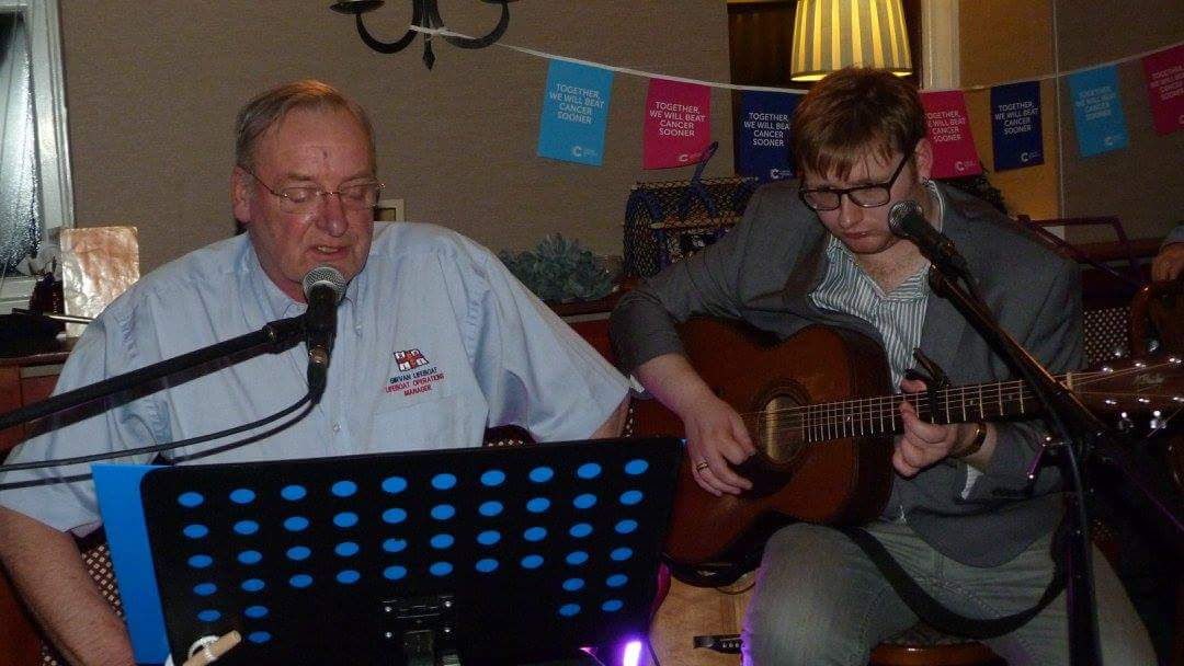 Lifeboat Operations Manager John Gourlay singing accompanied by event organiser and son JP Gourlay on guitar