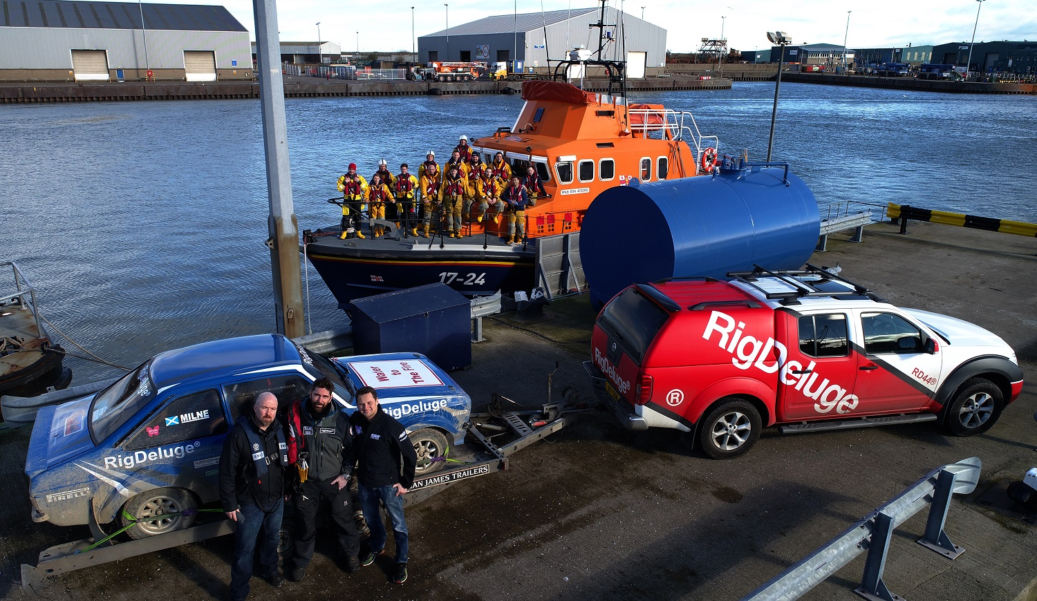 William Bird (Fennel Media), Ian Garden (RigDeluge) and rally ace Quintin Milne gather with their rally car, with Aberdeen Lifeboat crew lining the rails of their Severn class lifeboat behind