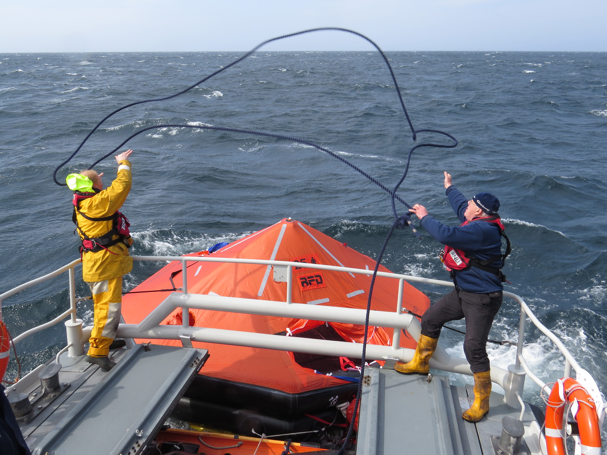 Two crew members lasso liferaft to secure to lifeboat