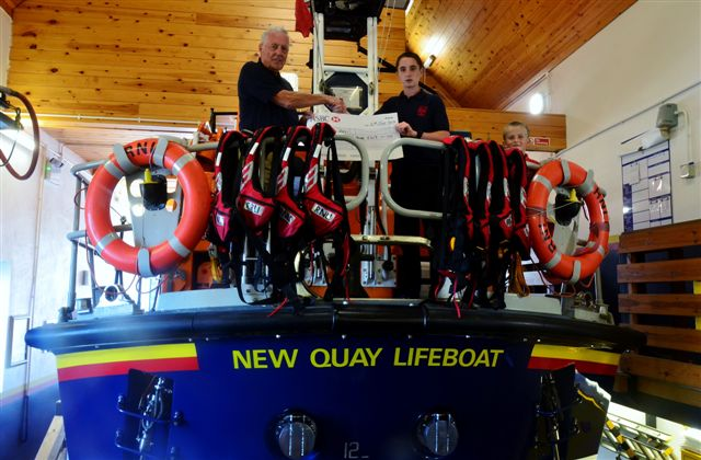 Daniel Williams aboard New Quay RNLI's Mersey class all weather lifeboat, the Frank and Lena Clifford of Stourbridge, handing over a cheque for £413 to Lifeboat Operations Manager, Roger Couch