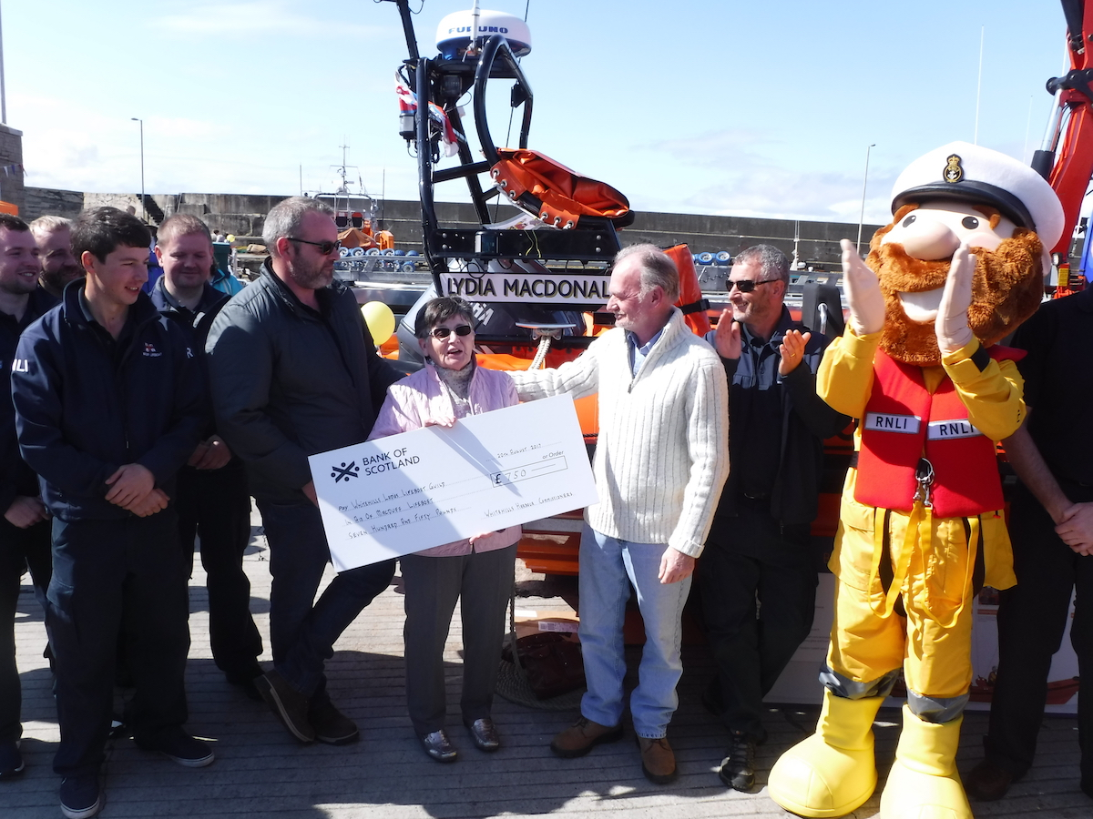 Whitehills Harbour Commissioners presenting the RNLI with a Cheque for £750 in front of Macduff lifeboat Lydia Macdonald with Stormy Stan