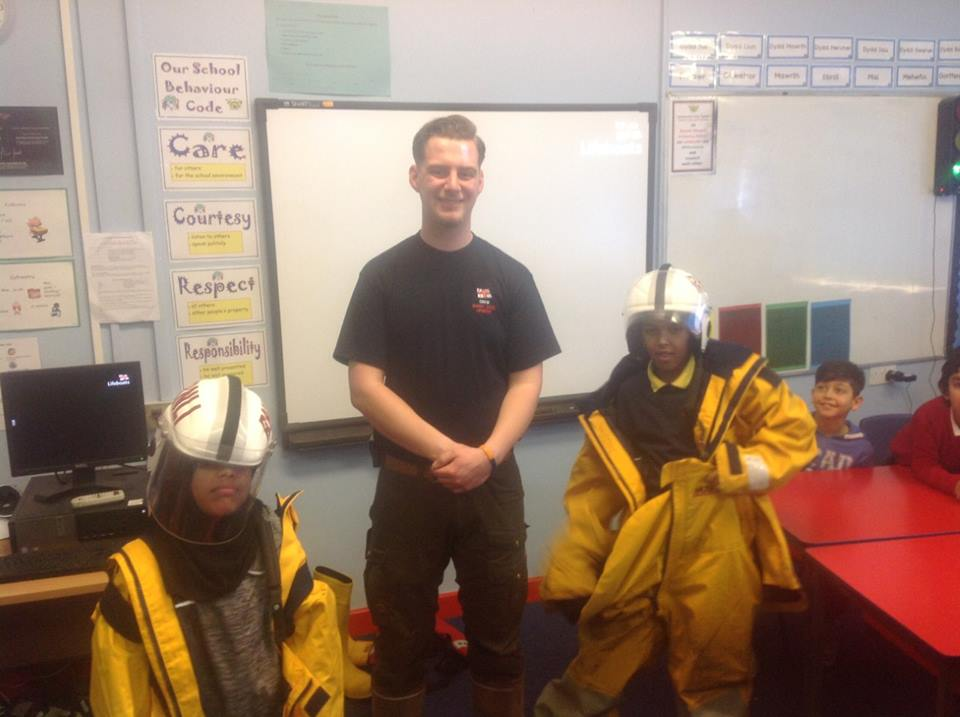 Mount Stuart Primary School pupils Hussein and Ola trying on lifeboat kit with Barry Dock RNLI Education Officer Ben Phillips