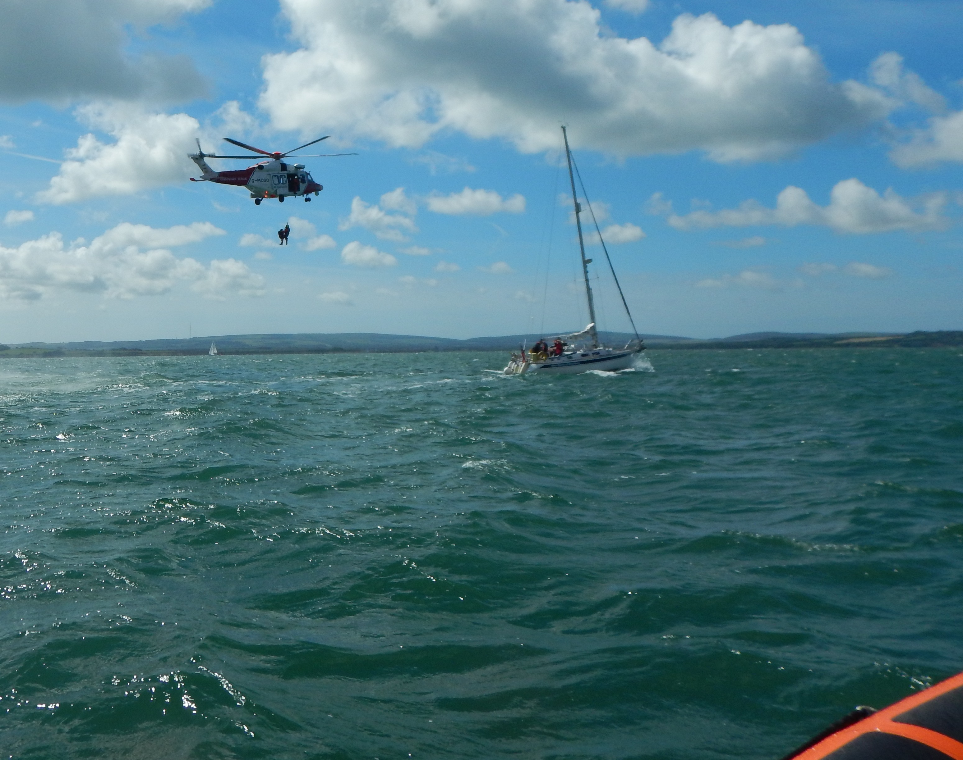 A paramedic assists in the helicopter rescue of the kayaker, with the lifeboat standing by.