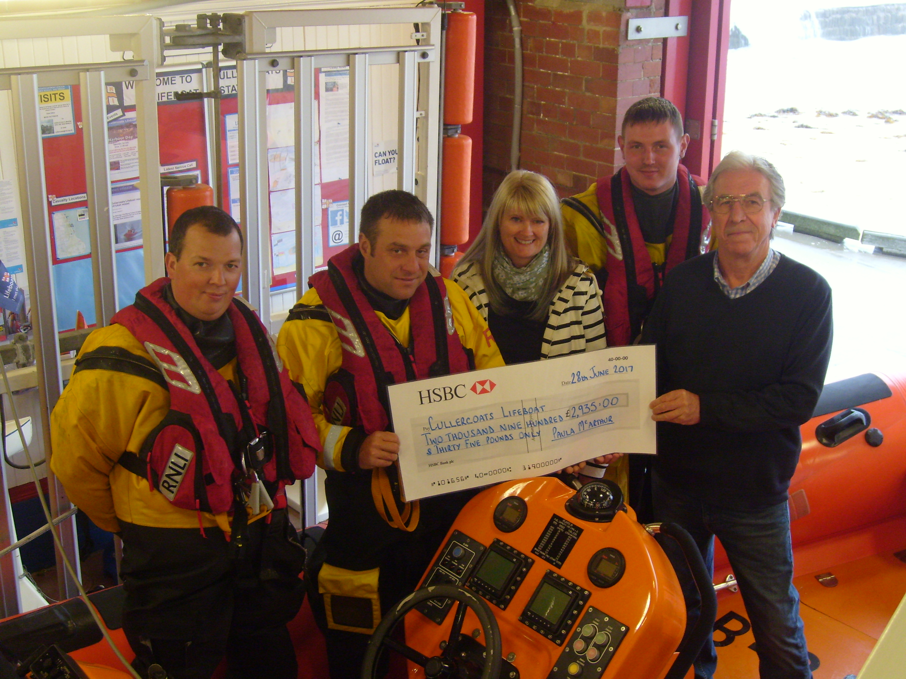 Paula presenting cheque to crew and Operations Manager