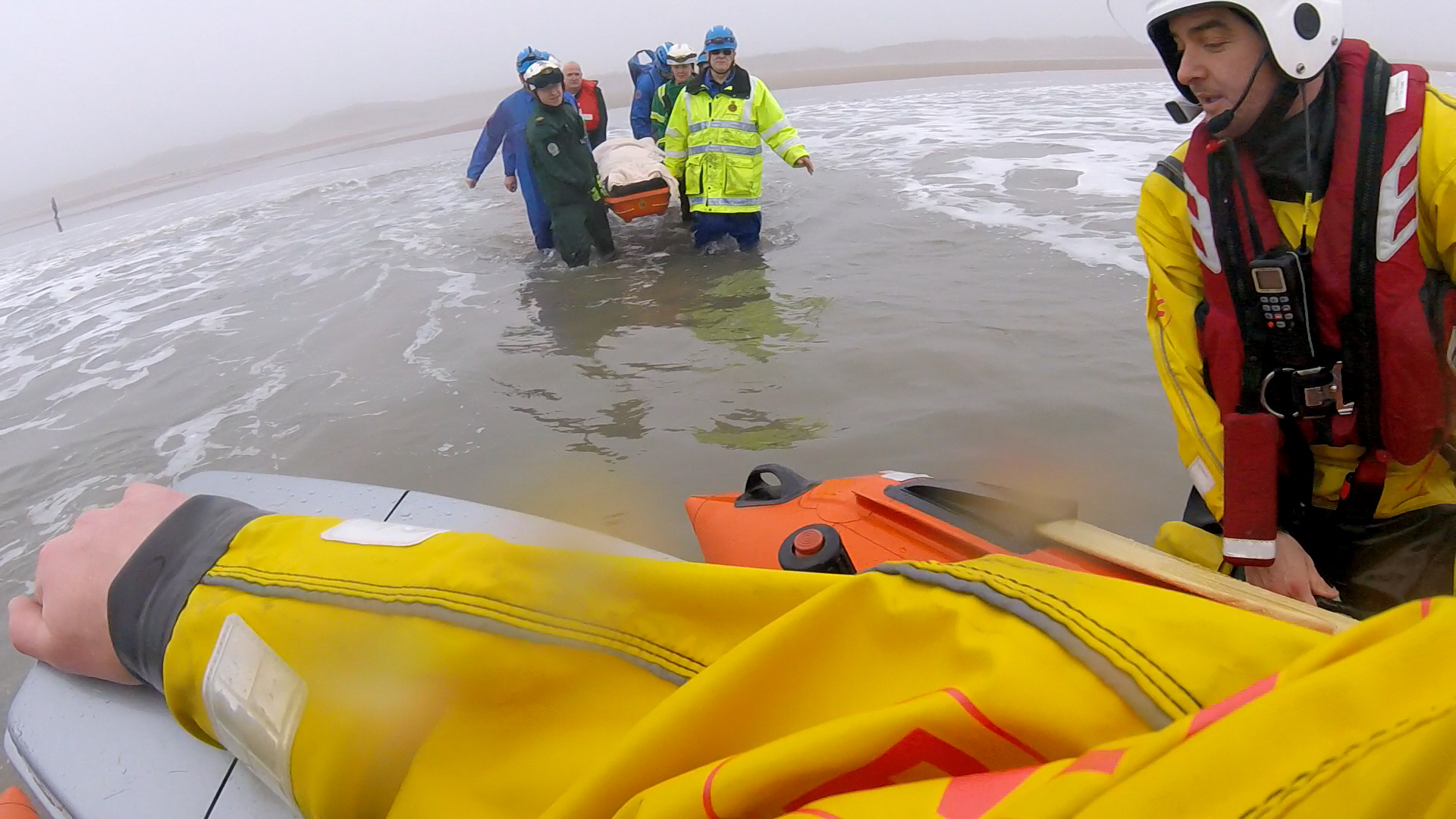 Multi agency personnel carry strechered casualty from the beach to the waiting D Class