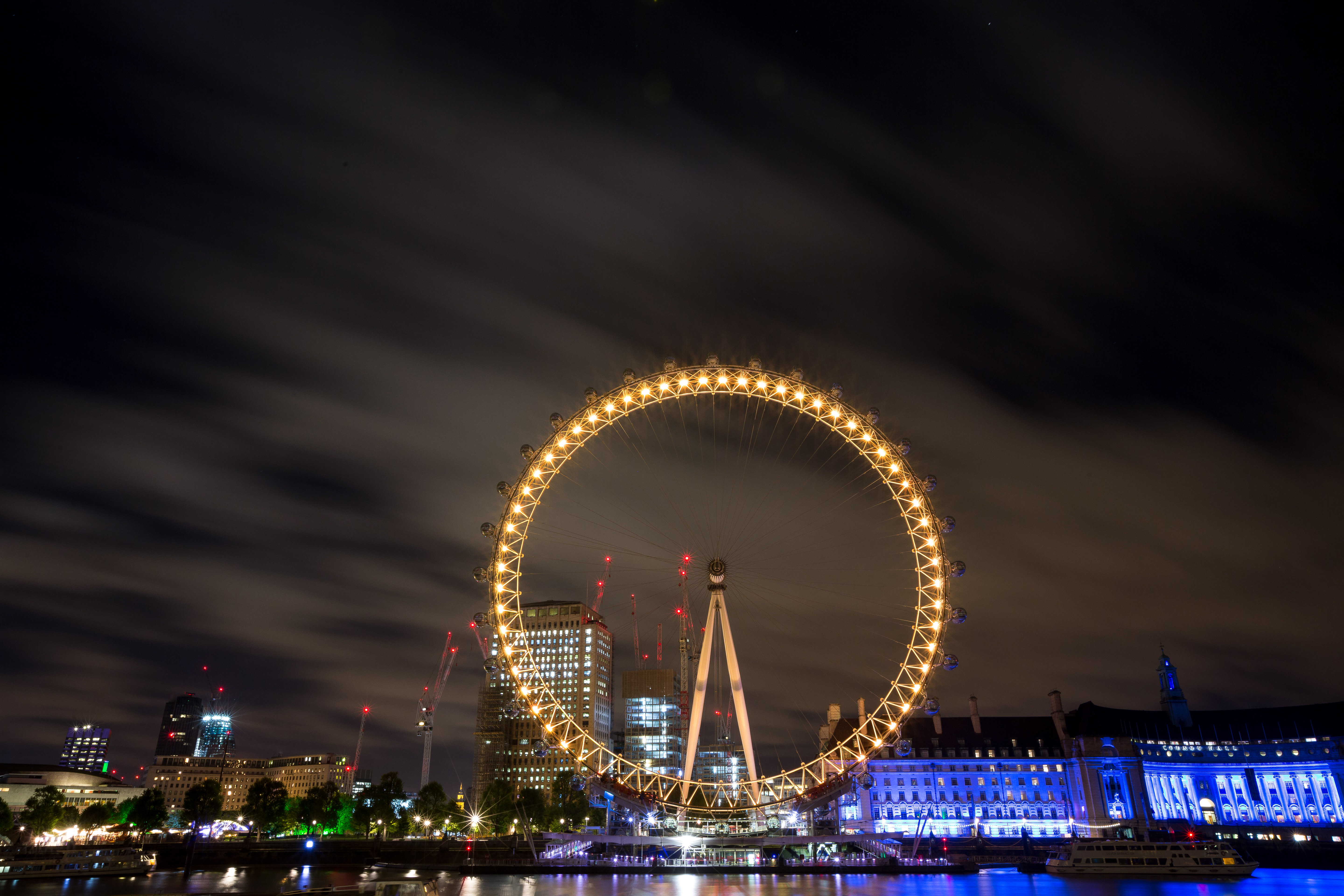 The Coca-Cola London Eye shines yellow in the London night sky