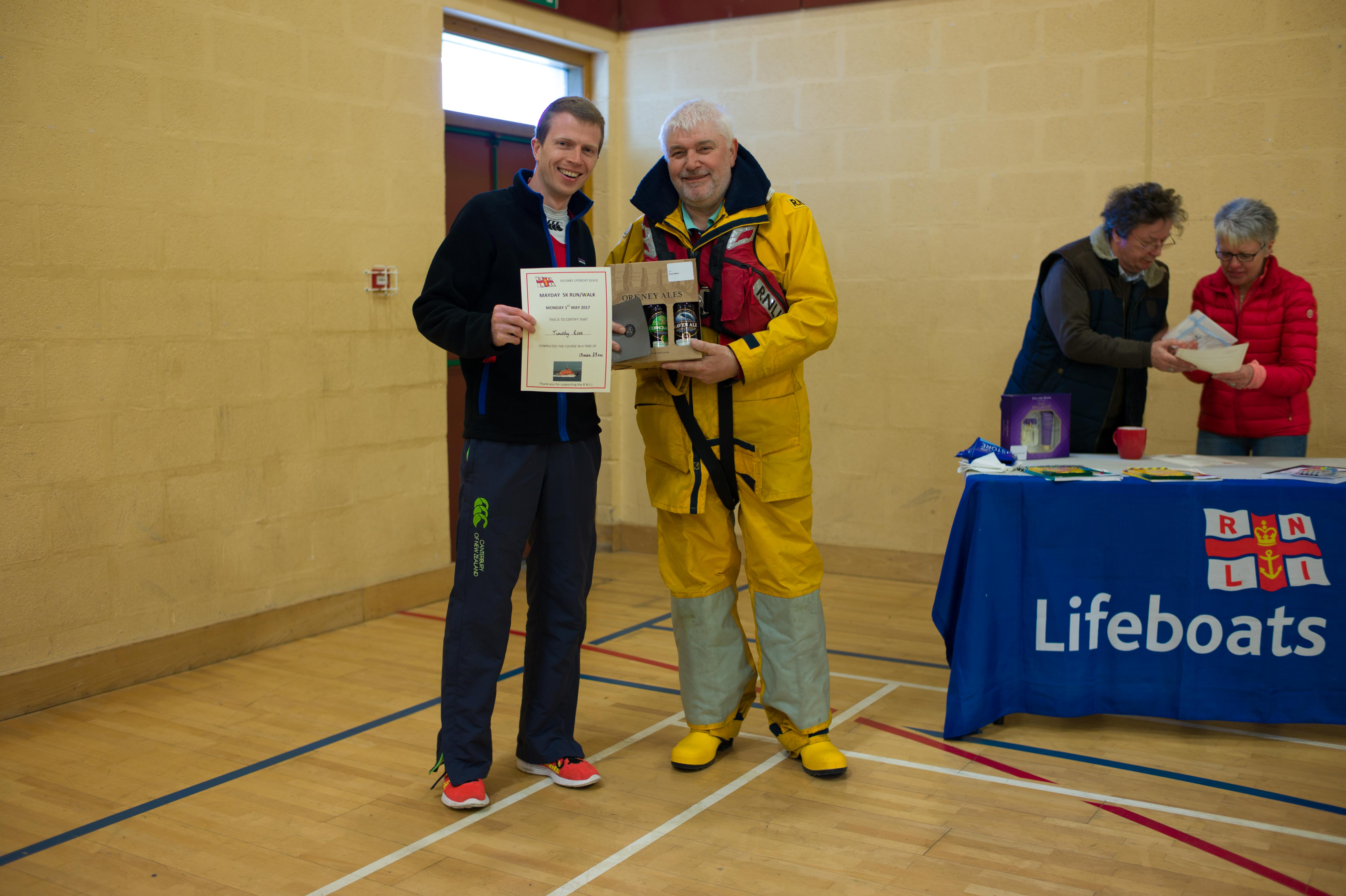 Photo shows Fred Breck standing alongside Tim Ross handing over beer and a certificate