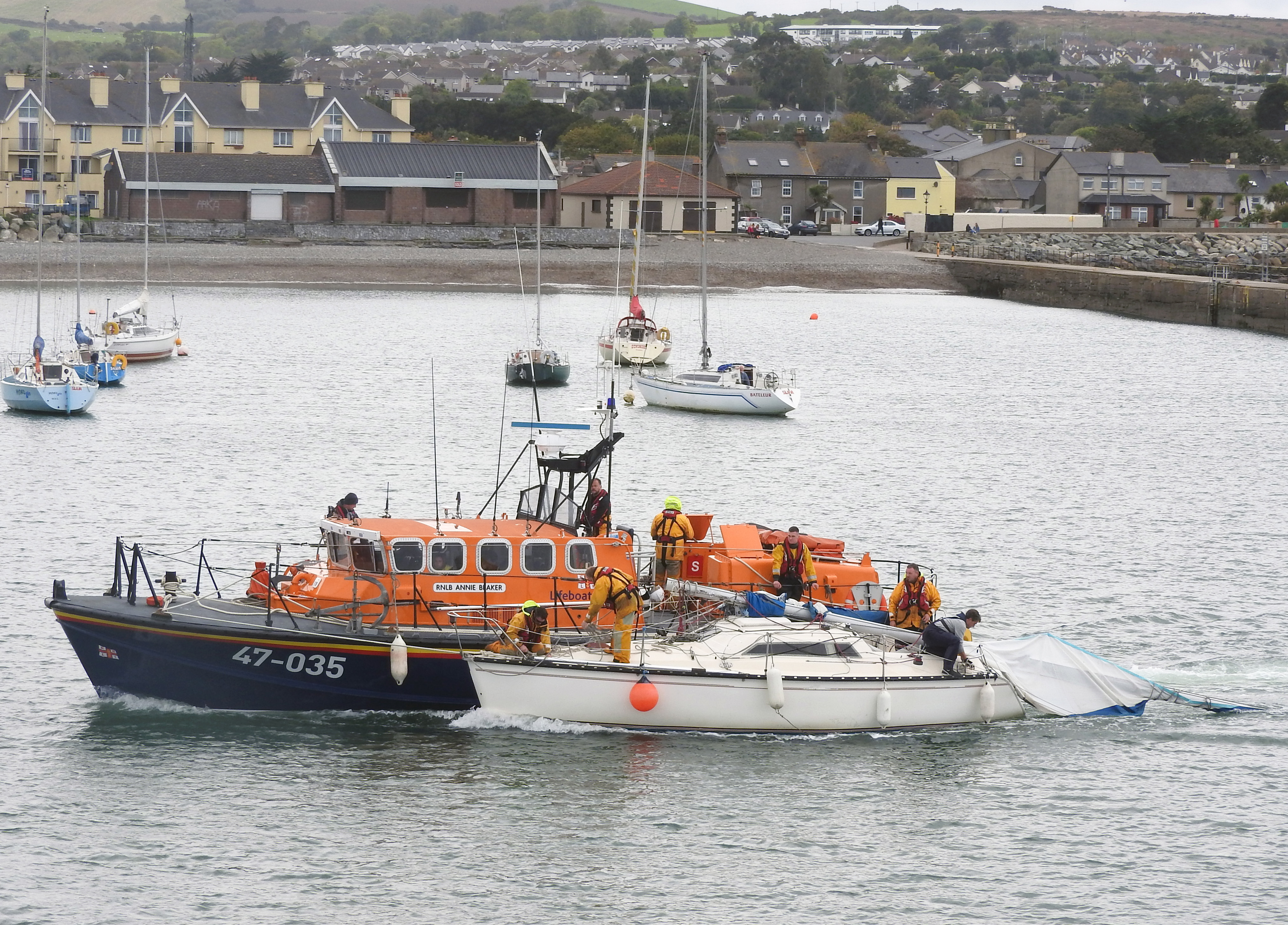 Wicklow RNLI all-weather lifeboat with the dismasted yacht at Wicklow harbour