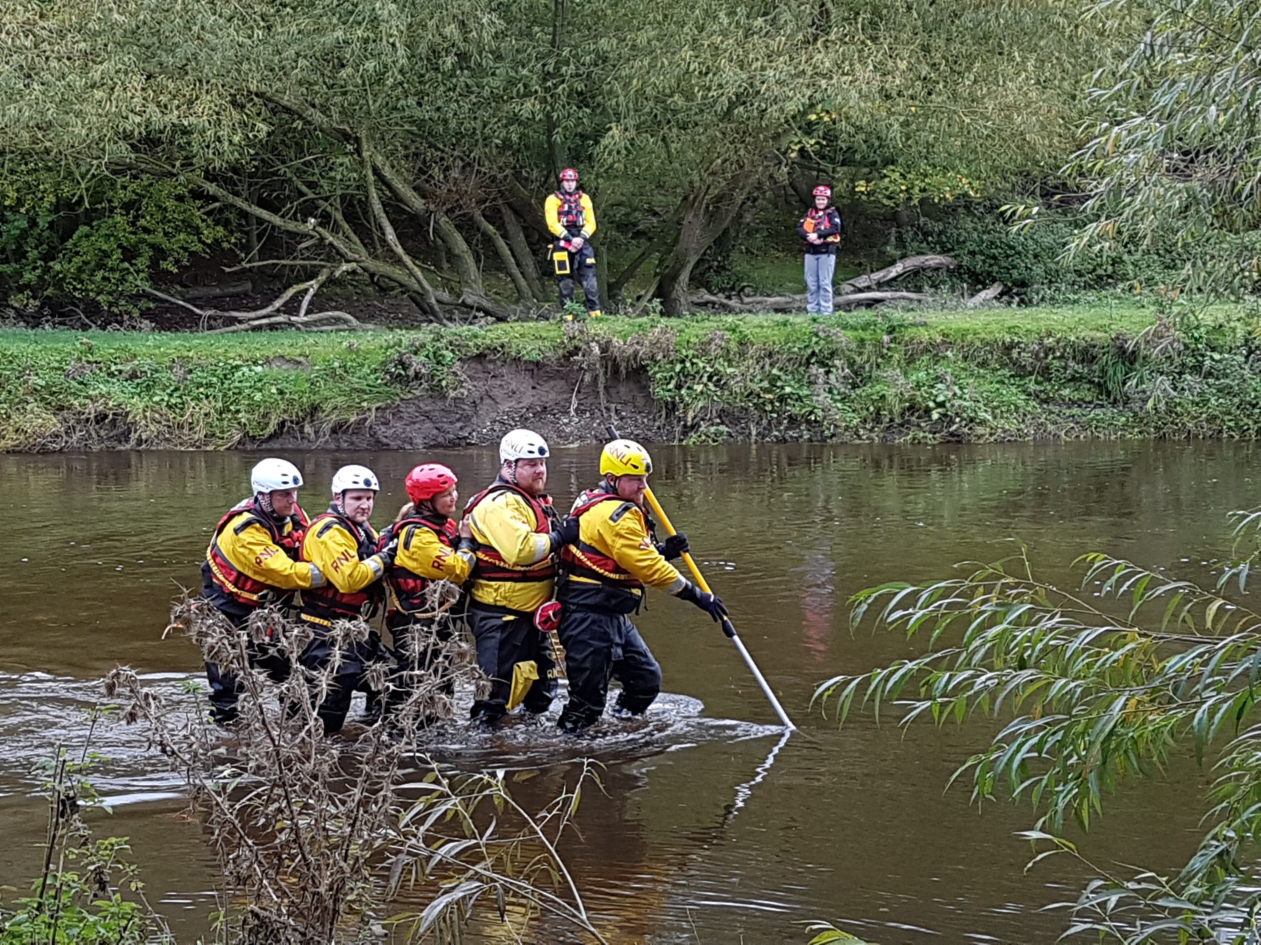 The RNLI Cumbria Community Flood Team practising wading in flowing water as part of the weekend's training exercise.