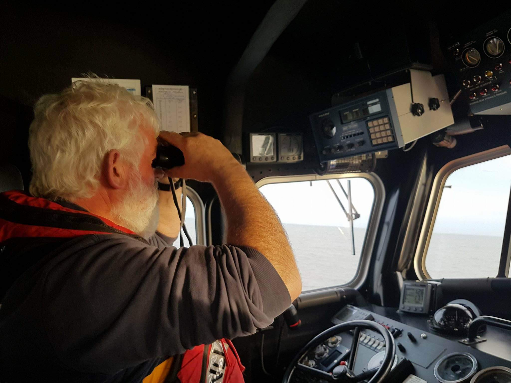 PICTURE OF CREWMEMBER SURVEYING FOR SIGHT OF CASUALTY VESSEL
