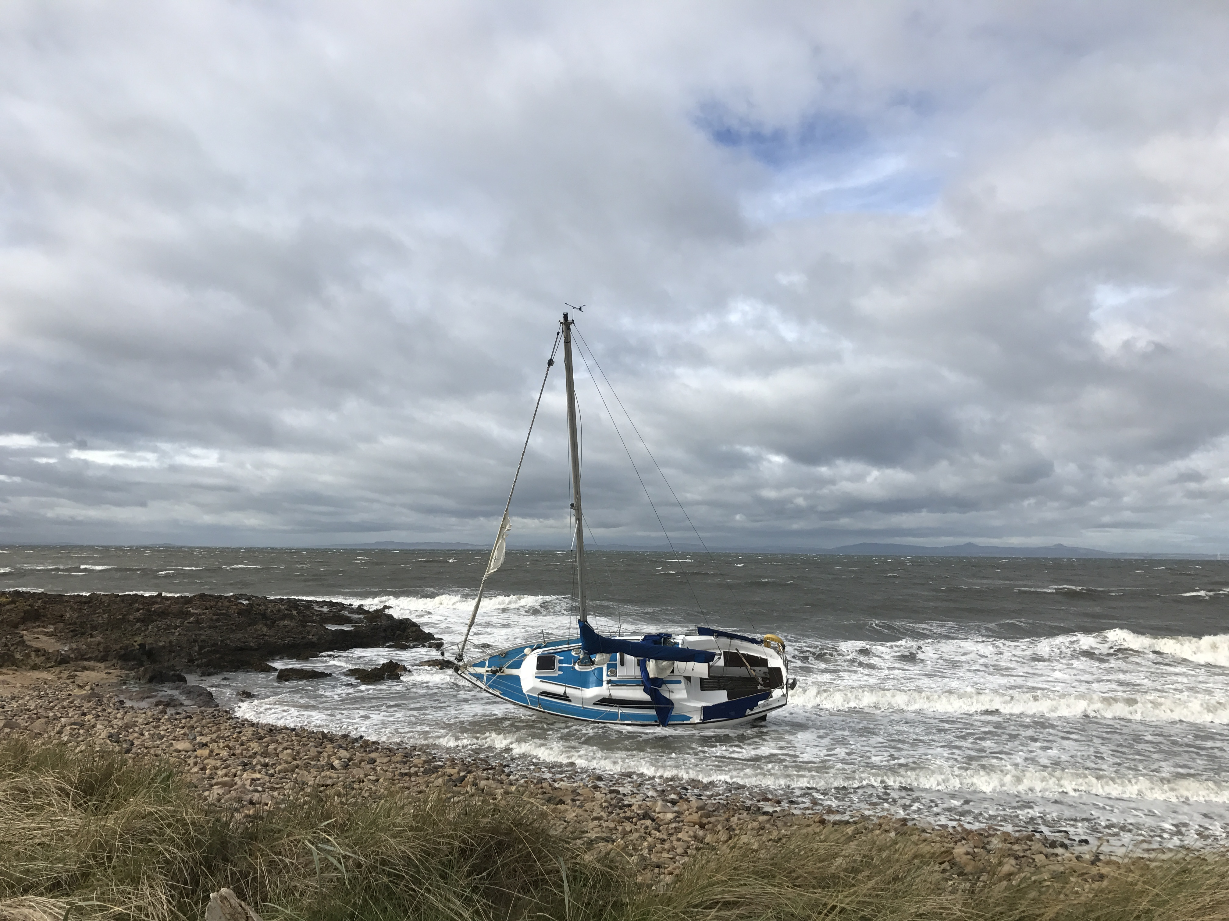 Yacht lying on its side with heavy seas in the background.