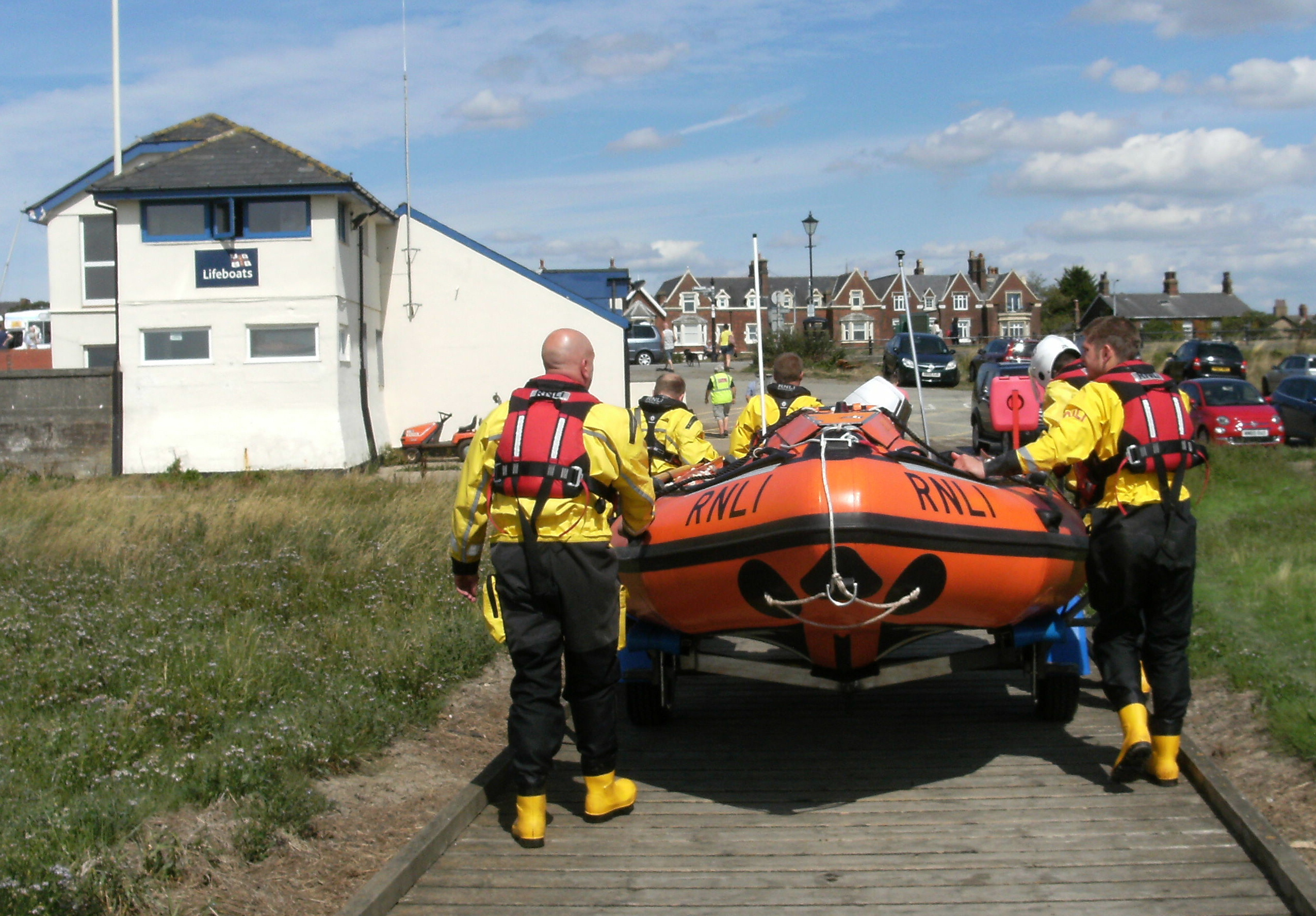 A group of lifeboat crew members pulling an inshore lifeboat along a wooden jetty towards her boathouse