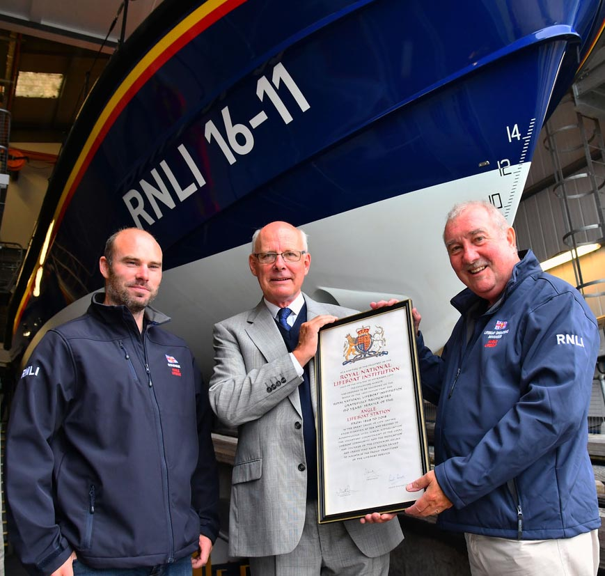 Rear Admiral Mark Kerr, Member of the RNLI Council, presents the 150 years anniversary vellum to Angle RNLI's Lifeboat Operations Manager, Julian Hammond (right), and Lewis Creese, Angle RNLI's Coxswain, at Saturday's open day.