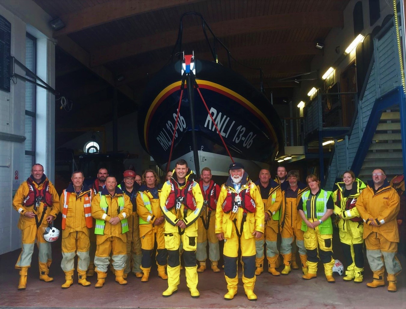 Councillor Geoffrey Watt, dressed in yellow RNLI all-weather gear and wearing his civic chain of office, stands with the Hoylake Lifeboat crew in front of the Shannon class lifeboat