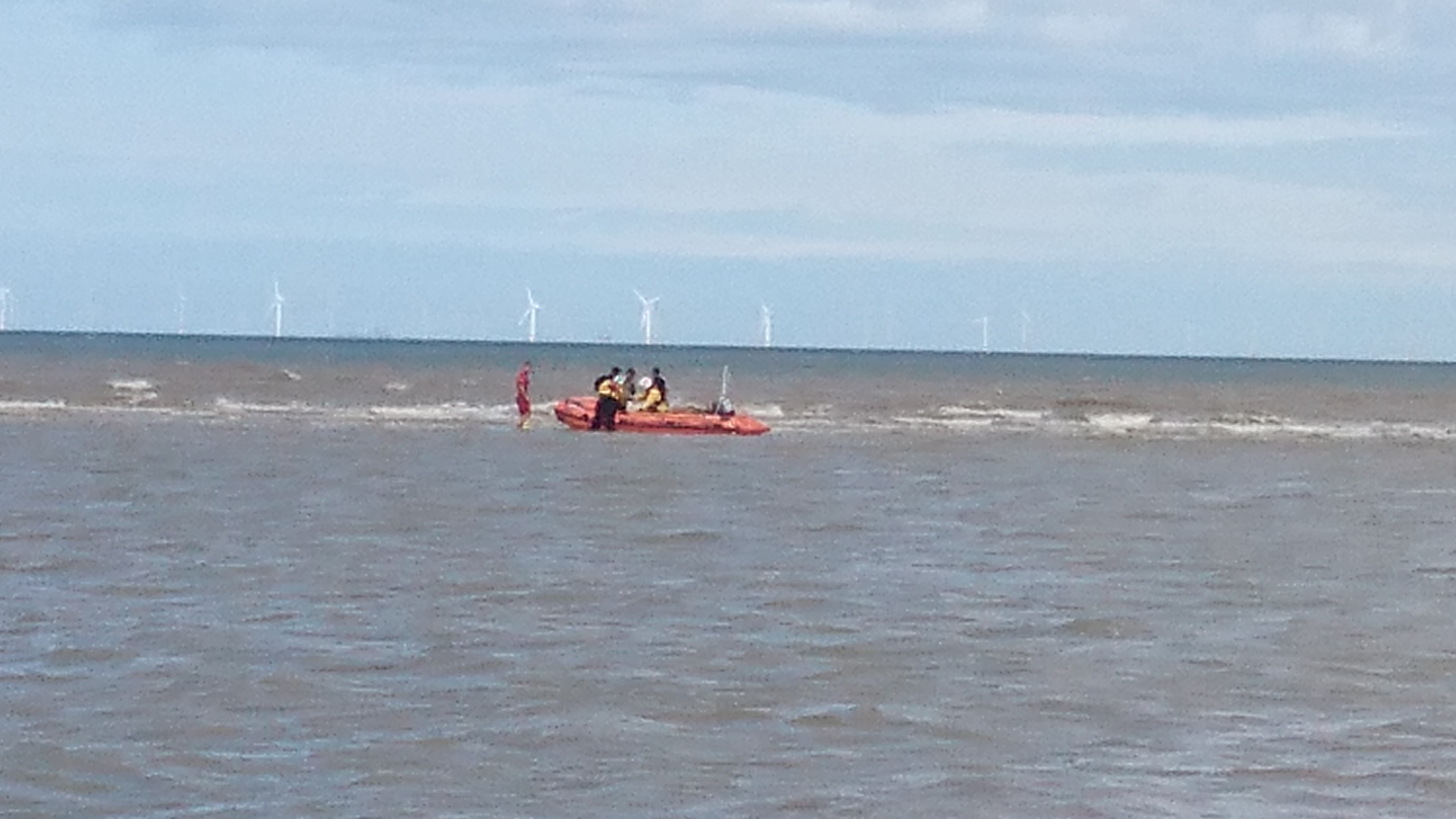 Rhyl inshore lifeboat and lifeguard get 3 youths on to boat from sandbank.