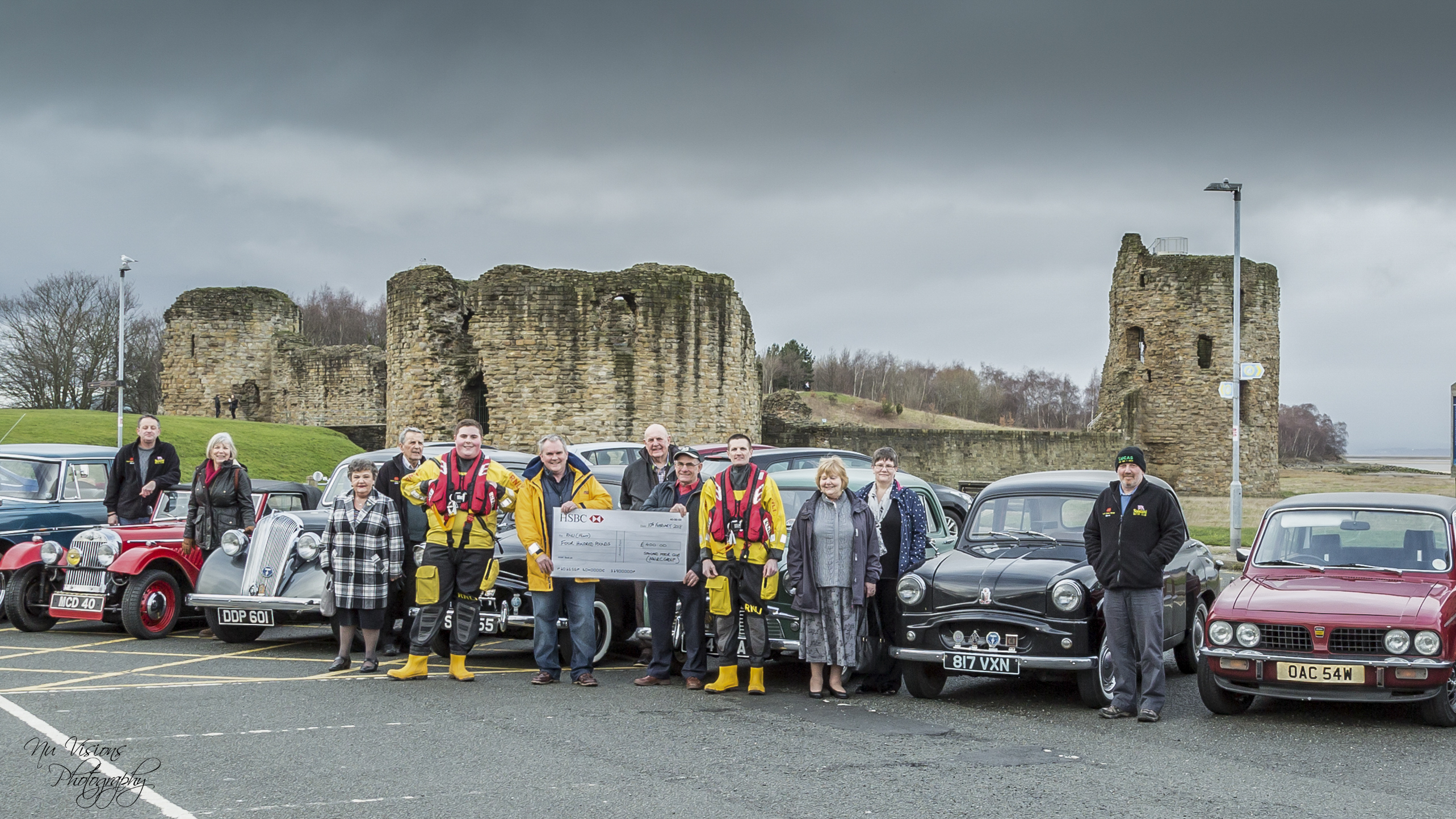 Members of the North Wales and Cheshire Standard Motor Club their vehicles, and RNLI volunteers accepting a cheque for £400