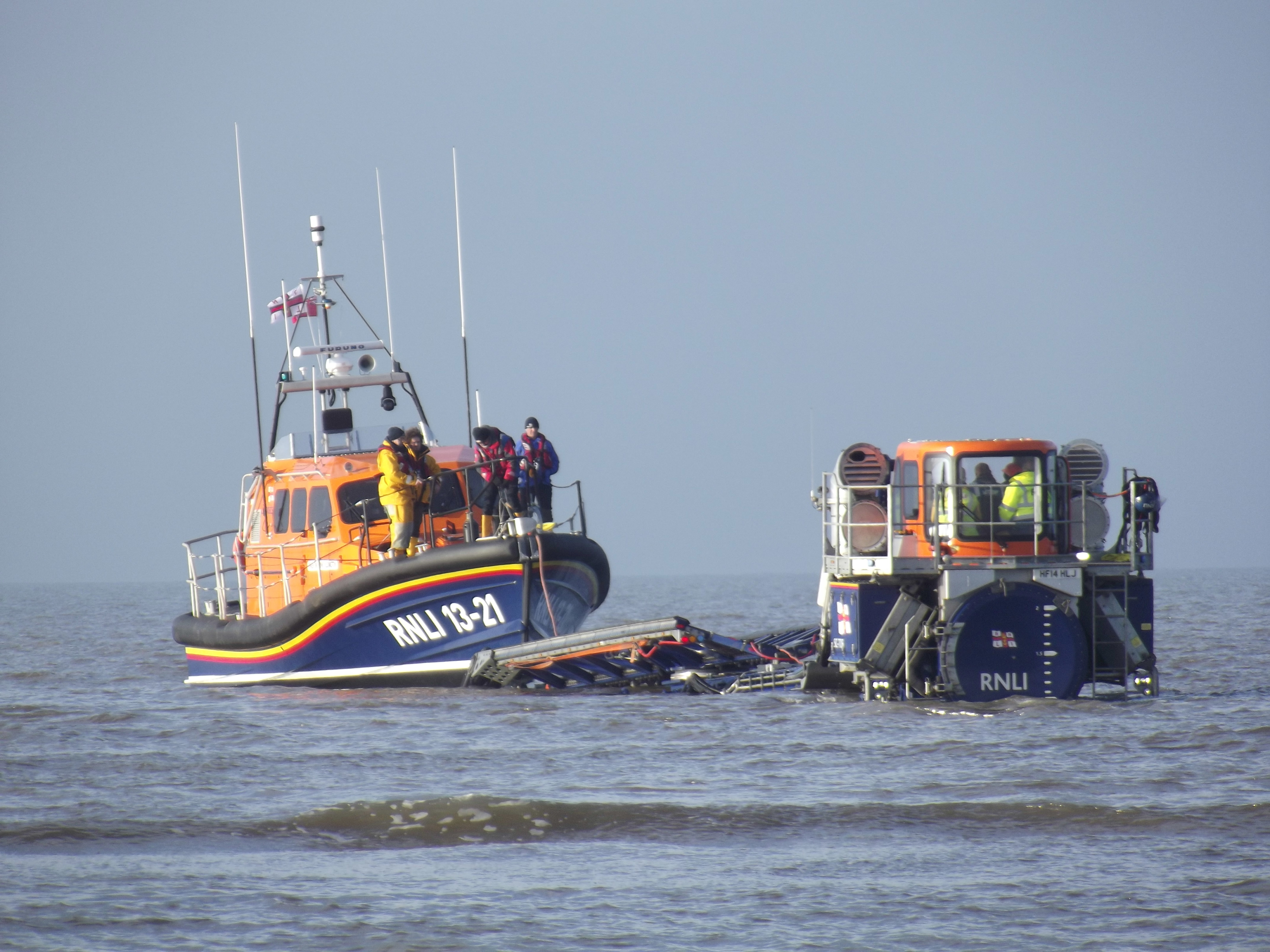 "A lifeboat is being recovered from the sea by a ""tractor and carriage system"""
