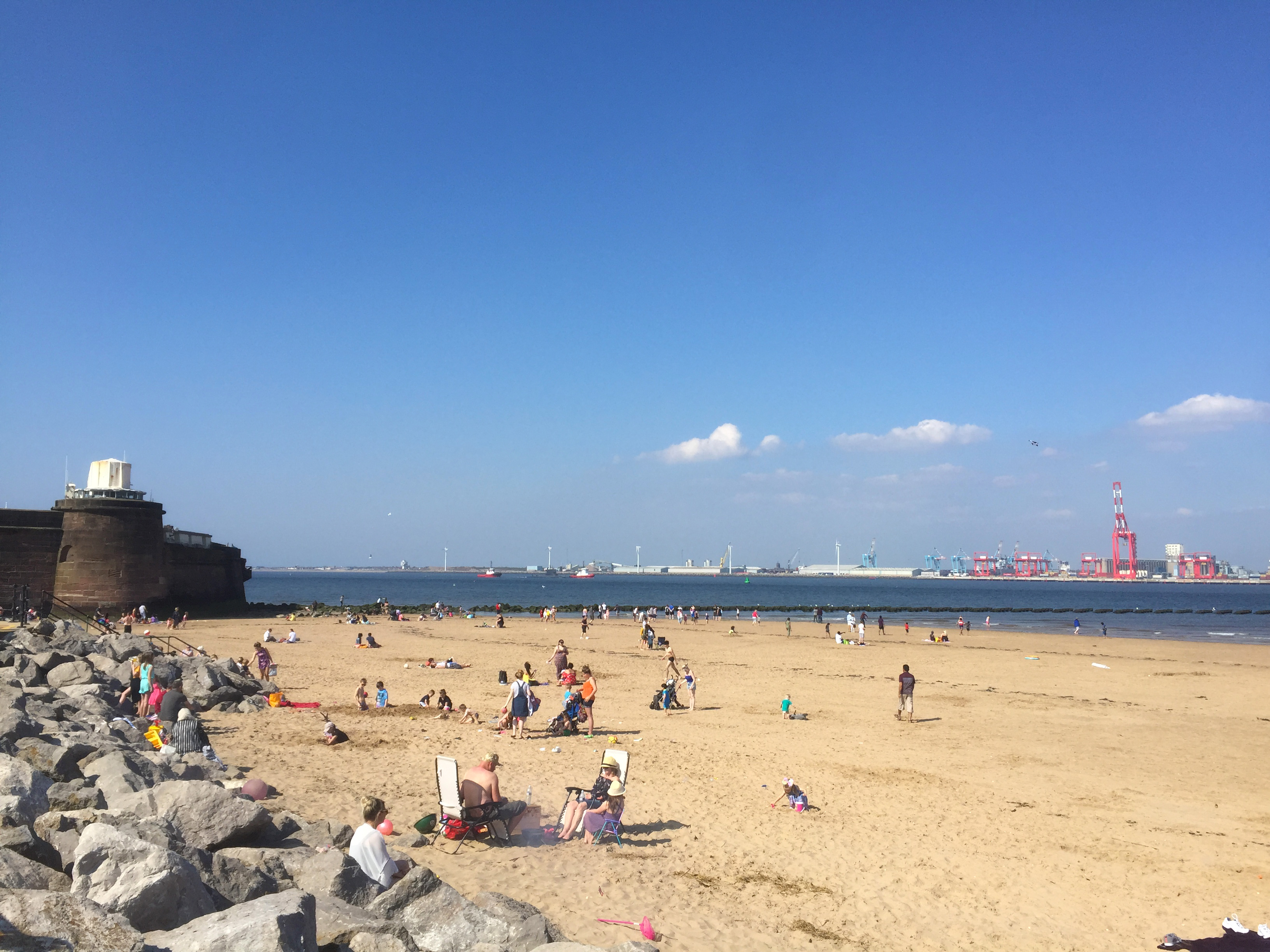 Blue sky overhead with Fort Perch Rock in the distance,rocks on the left and to the right an expanse of sand busy with people and a glimpse of the sea