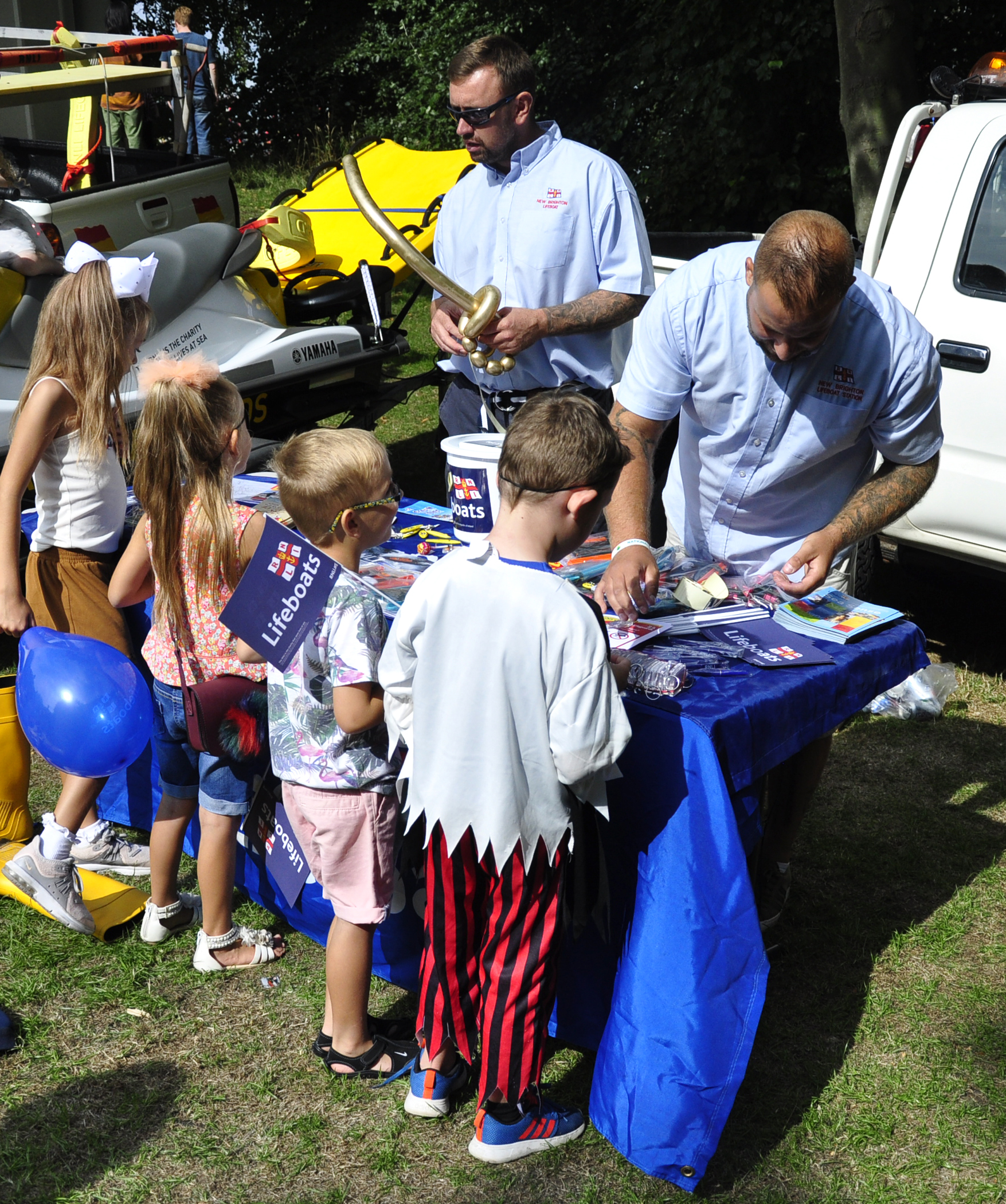 Four small children stand with their backs to camera at a table covered with RNLI memorabilia and literature