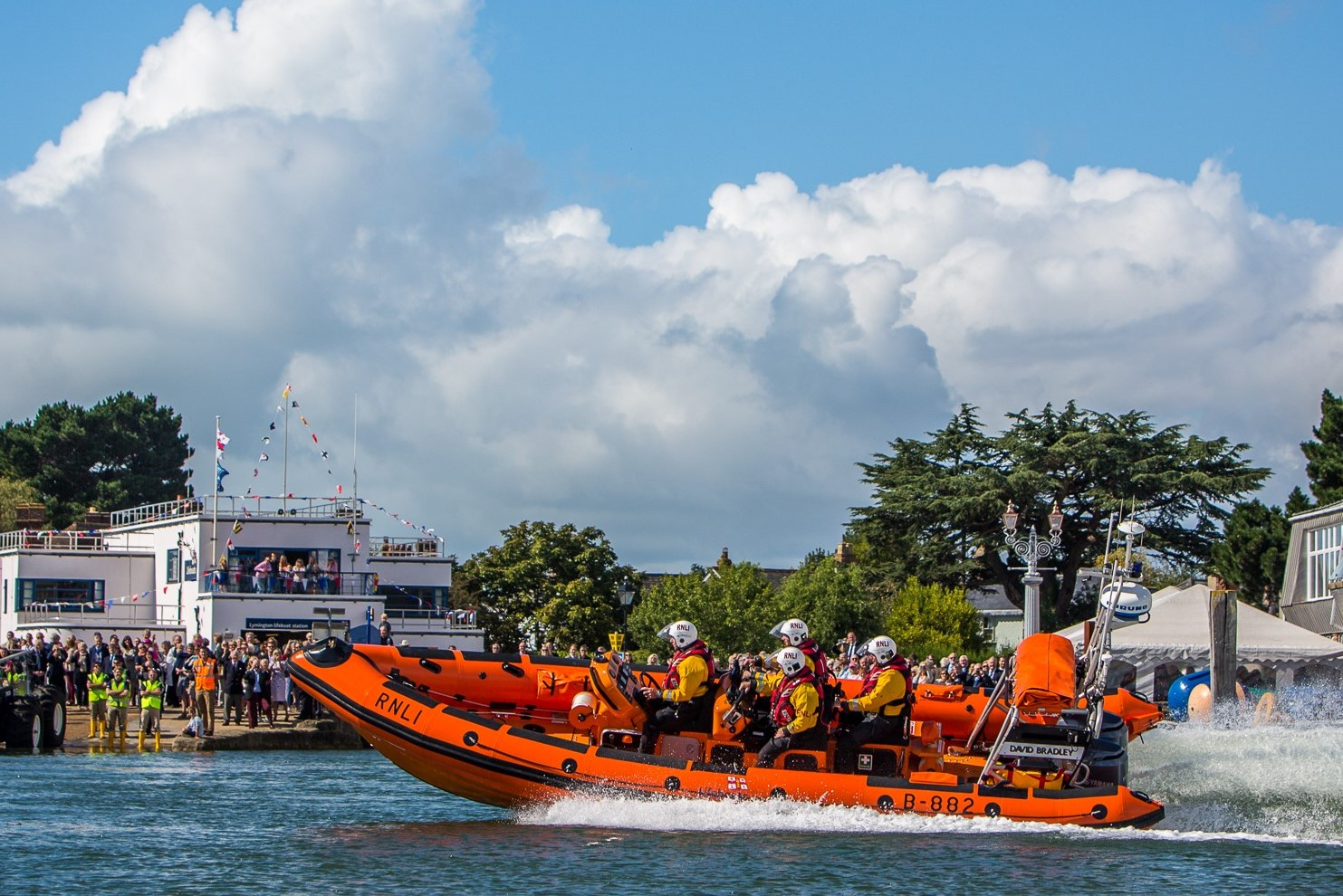 Lymington RNLI Lifeboat at speed in foreground, Blue sky with fluffy clouds background