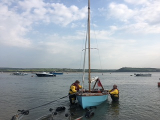 Wooden sailing boat being recovered to shore following rescue by Rock RNLI lifeboat