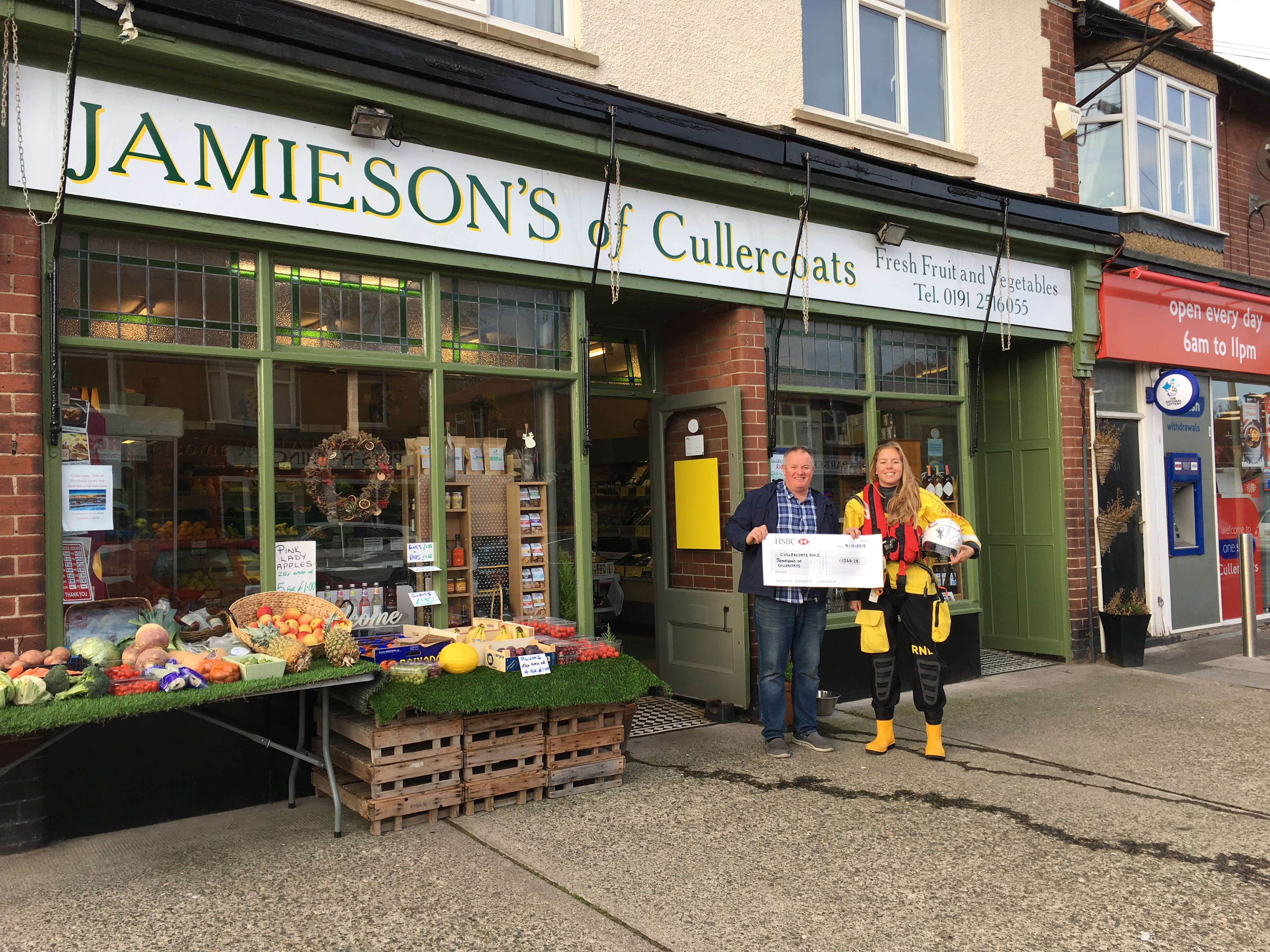 Fundraiser Dave Jamieson and Cullercoats Crew Member, Anna Heslop, stand outside Jamieson's of Cullercoats