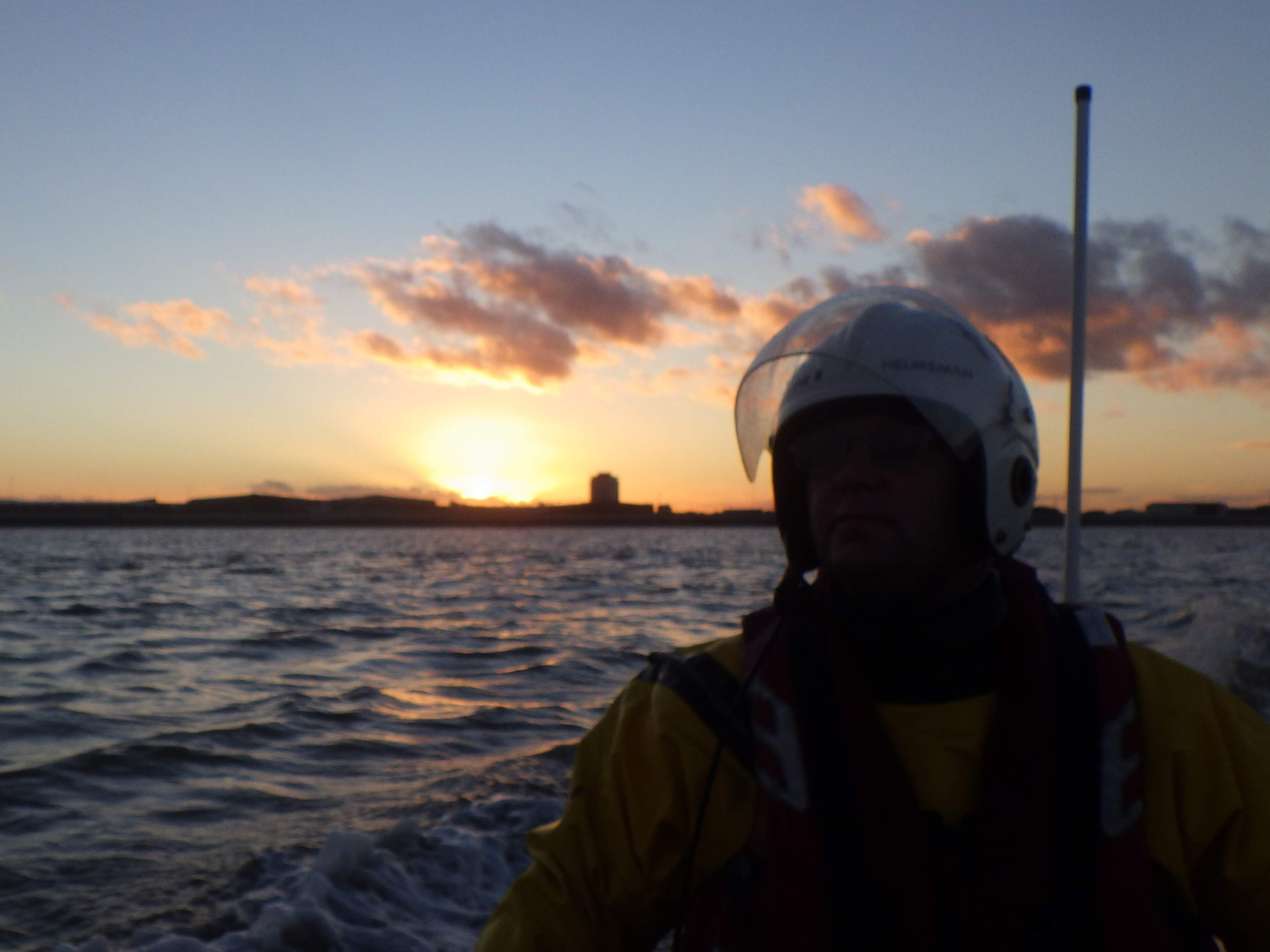 Sunset from lifeboat with helm visible in silhouette
