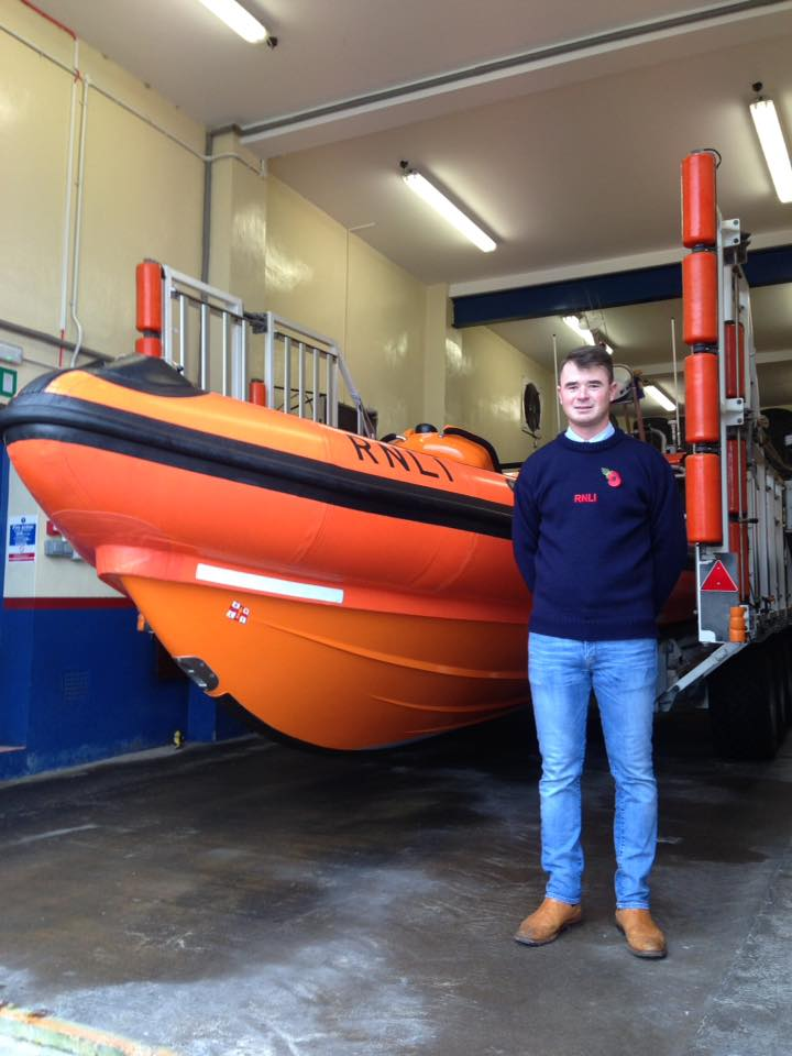 Will Bell at Flamborough RNLI boathouse, standing in front of the B class lifeboat