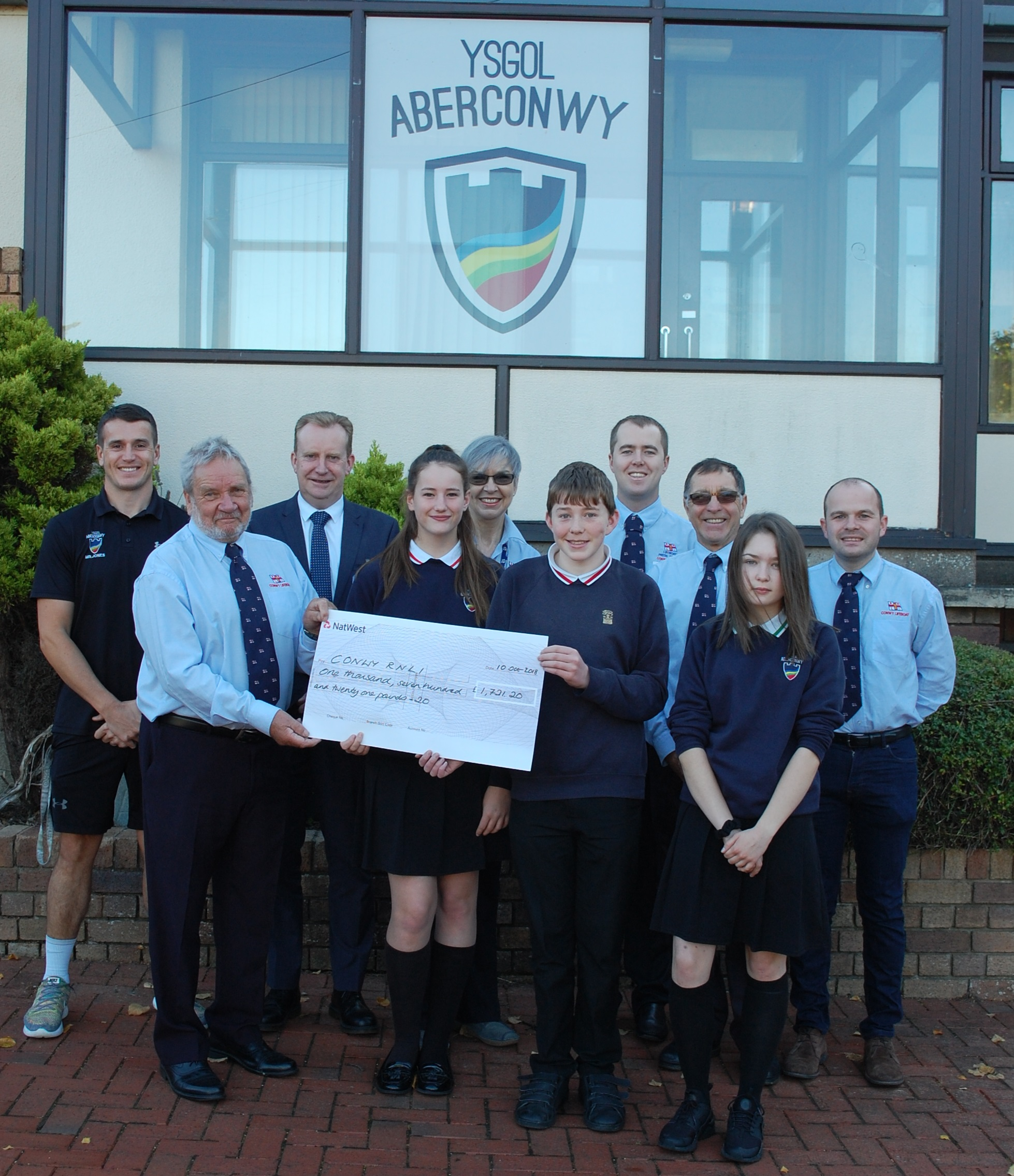 Staff and pupils pictured outside school handing over cheque to Conwy RNLI volunteers.