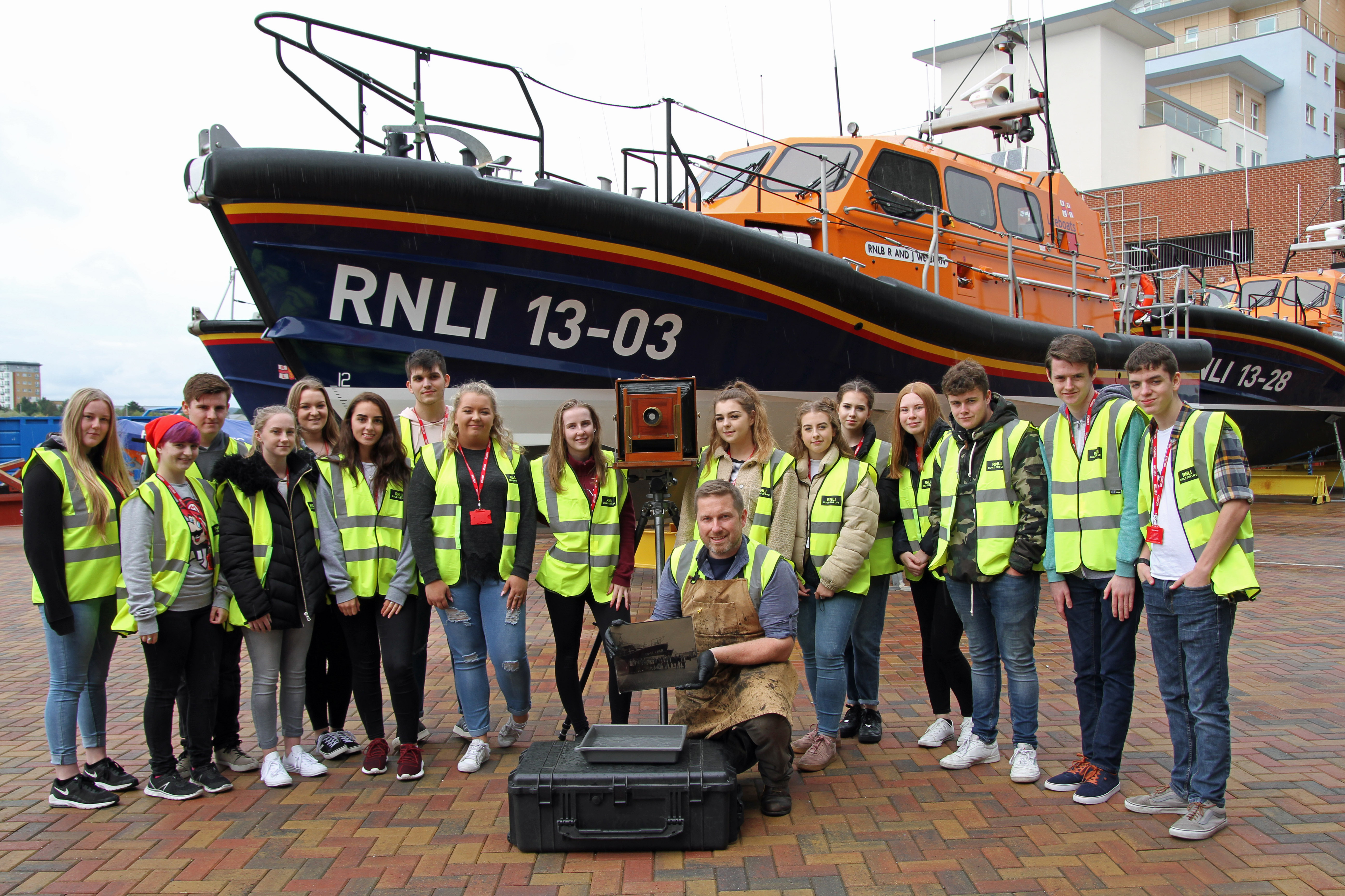 Jack Lowe and photography students from Poole High School at RNLI. Jack holding glass plate.