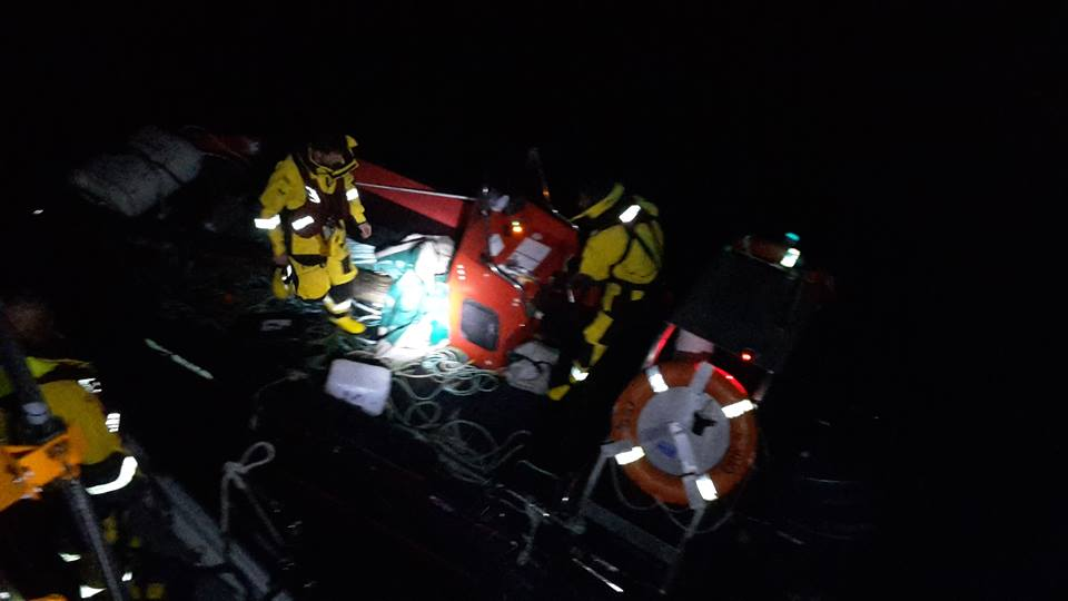 Night photo of crew members inspecting the rib and making ready for tow.