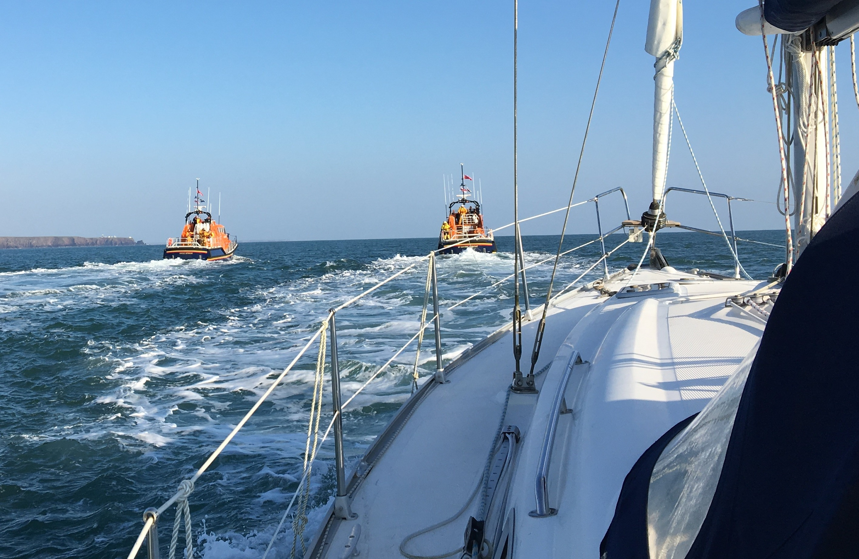 Broken down yacht is towed by St Davids RNLI with Angle RNLI ready to to take over the tow.