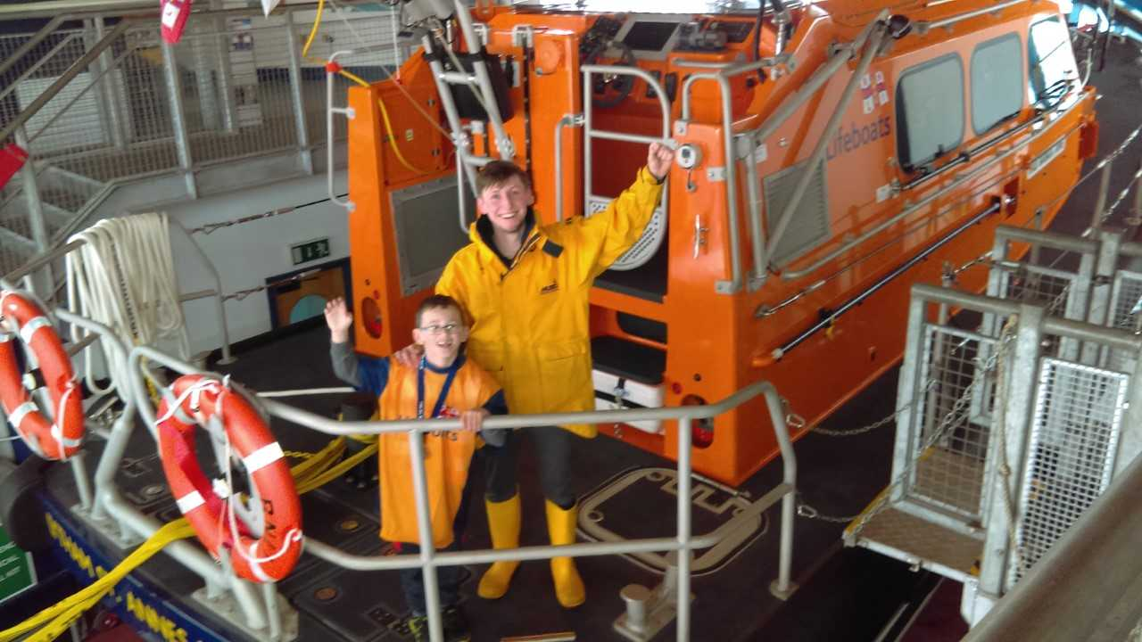 a young boy and a lifeboat crew member stand on a lifeboat
