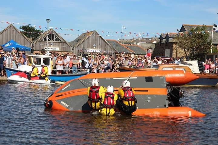Bude volunteer lifeboat crew demonstrating righting a capsized vessel in front of crowds on Bude canal