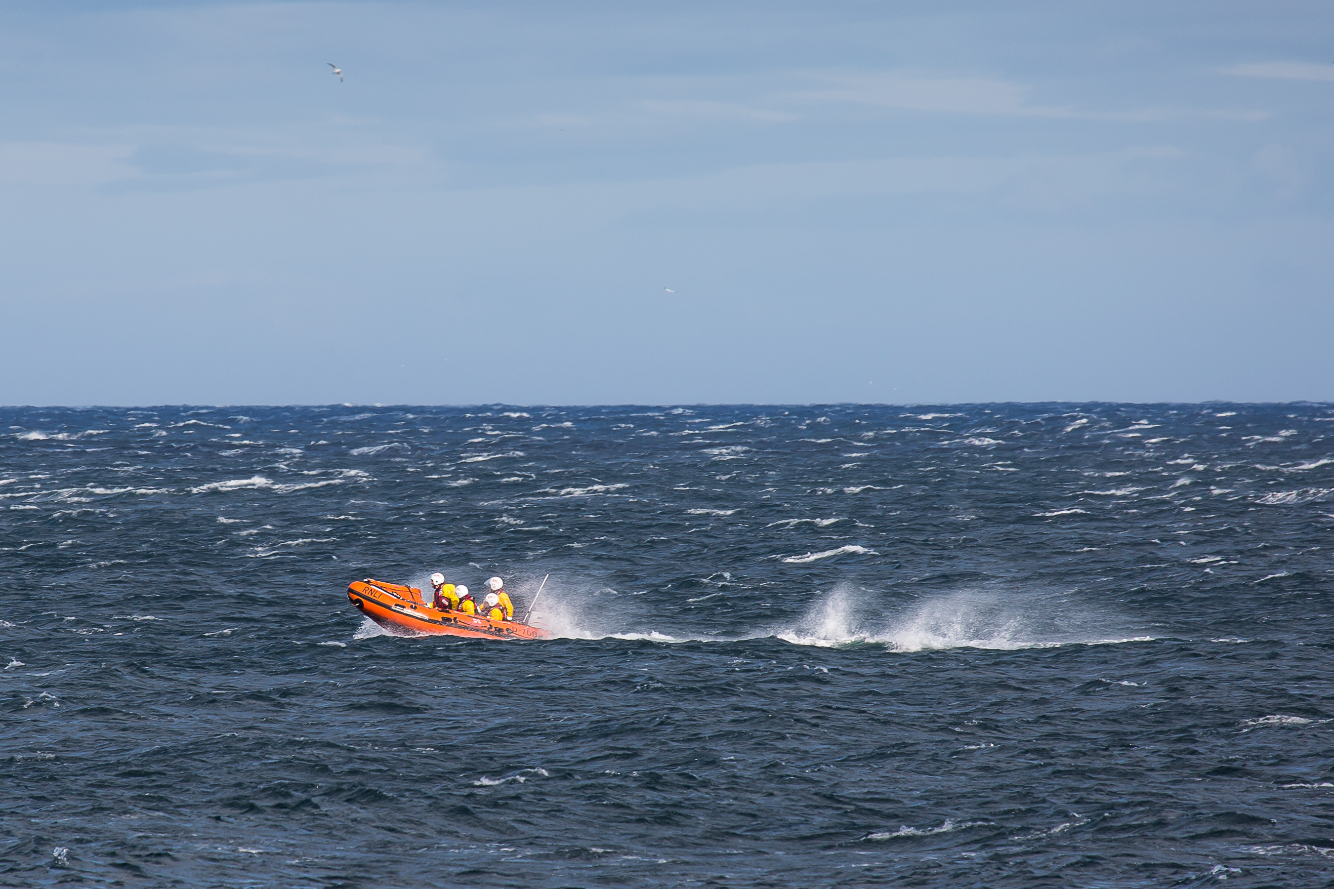 Dunbar ILB races through rough conditions to locate casualty. Blue skies overhead and excellent visibility. The azure blue sea is rough and capped with many white horses. The bright orange boat with it's bow risen in the surf travels from right to left and is followed by a heavy wake that is broken by the strong wind creating a lot of spray. 4 crew members are visible on board.