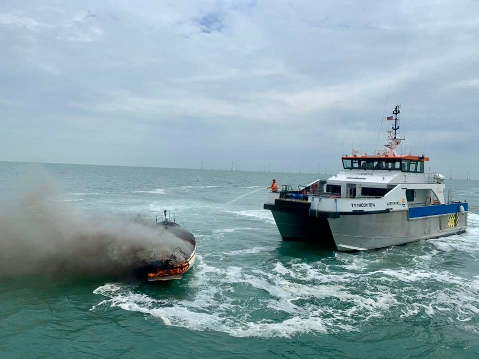 A burning yacht being hosed down by an attending Wind Farm vessel.
