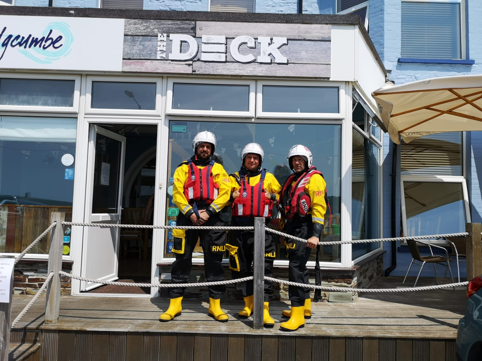 Three volunteer crew members in lifeboat kit outside the Deck bar and restaurant in Bude