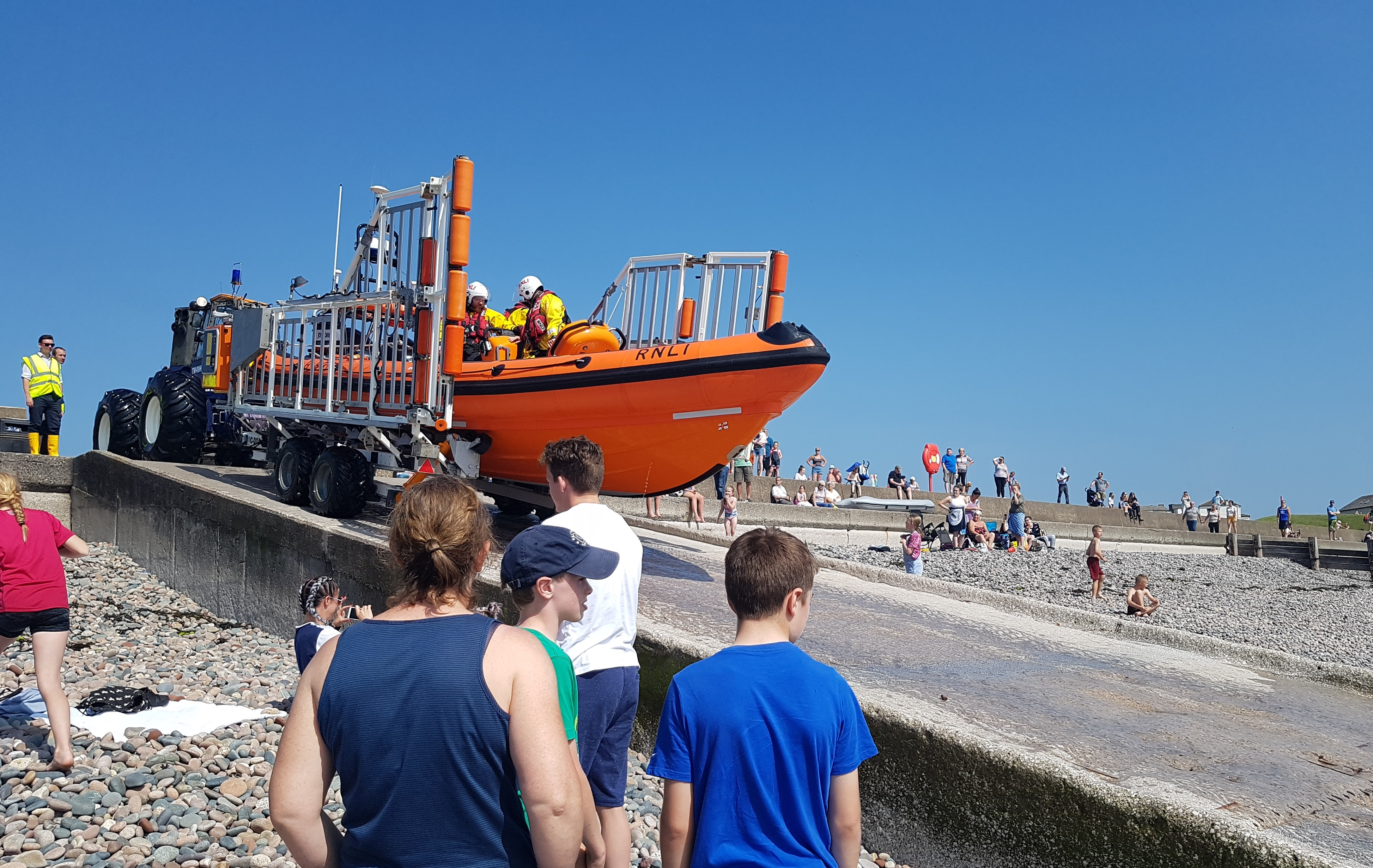 Returning back to the lifeboat station watched by holiday makers and locals enjoyng the sun.