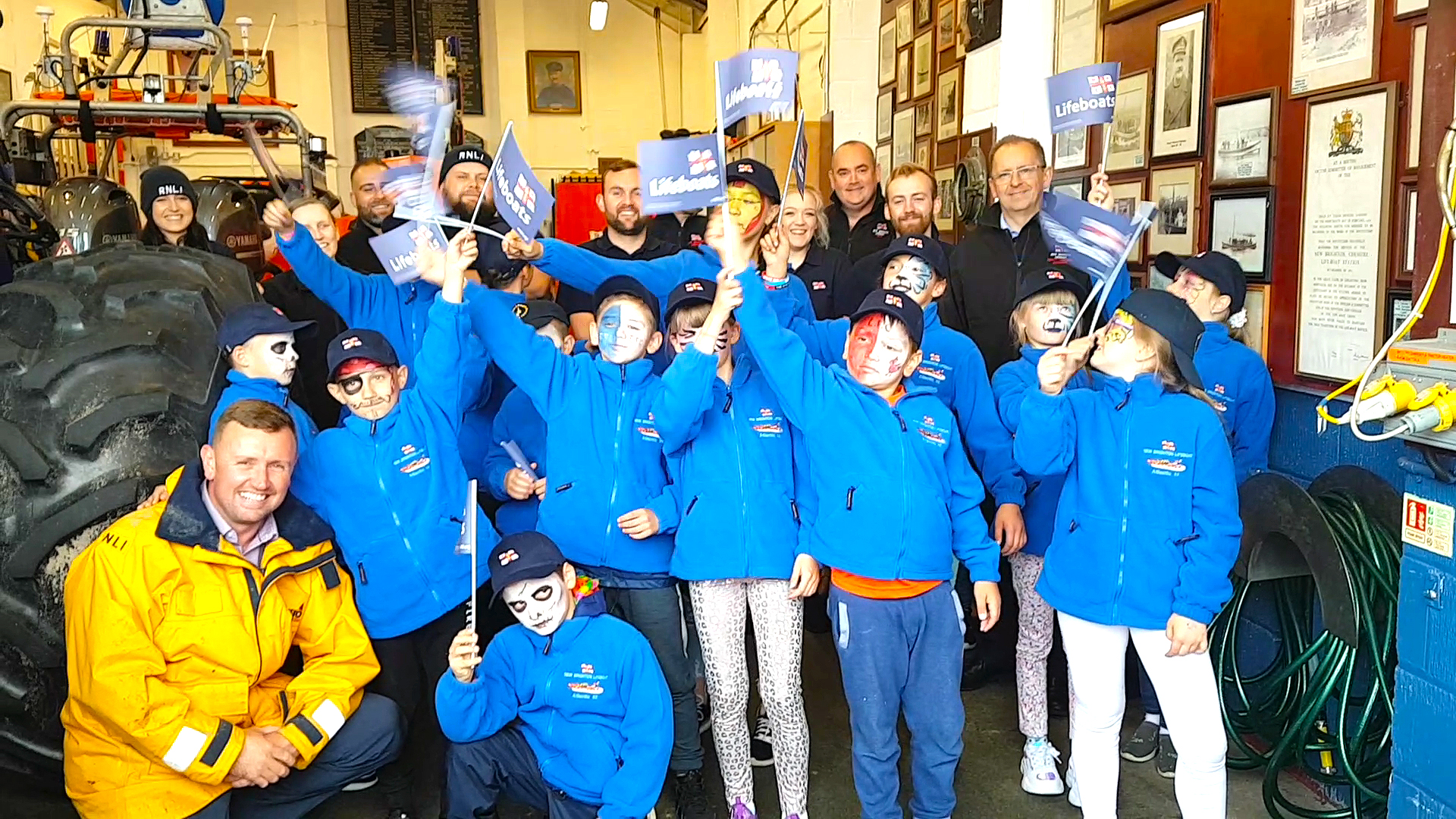 Group picture with the children wearing fleeces and hats while waving RNLI scarves