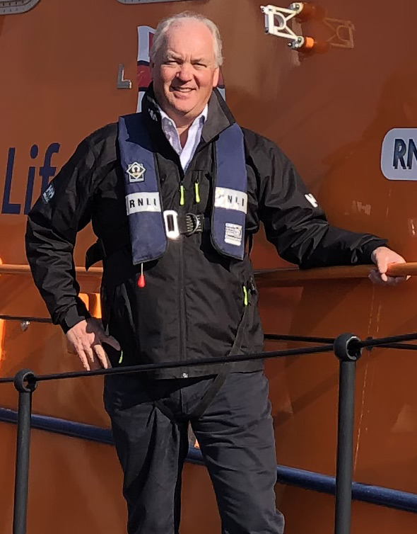 Mark Dowie stood on the side of Salcombe RNLI's Tamar class lifeboat