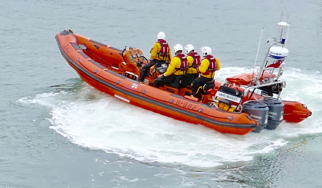 Lymington RNLI Atlantic 85 with white water at stern and Grey seas