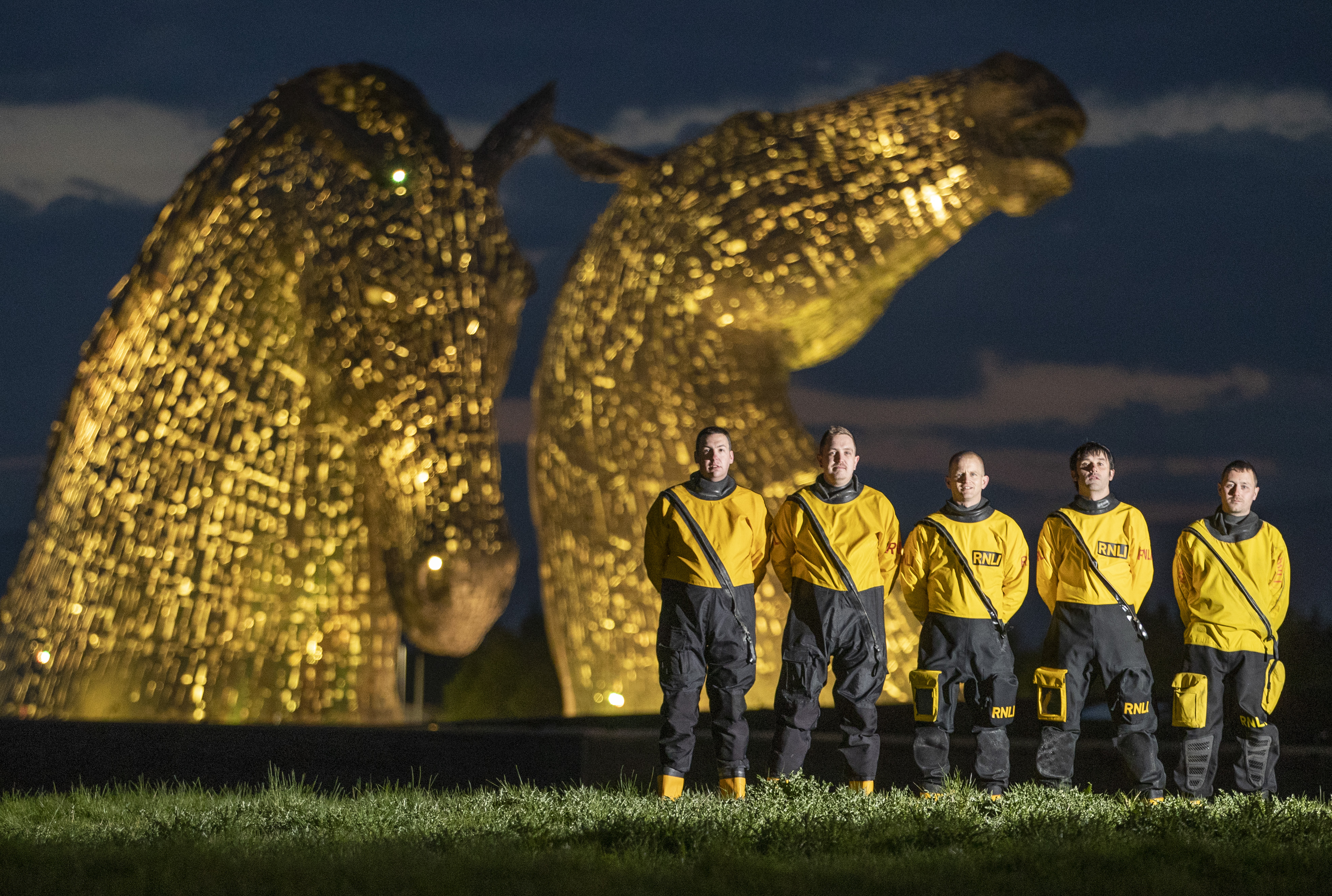 RNLI volunteer crew from Queensferry and Kinghorn collect in front of The Kelpies as they light up yellow for Mayday