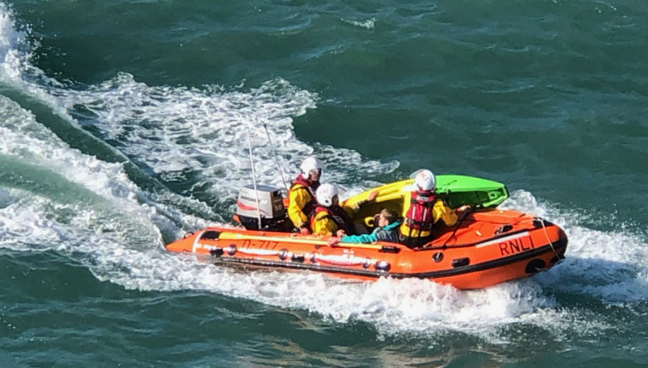 Inshore lifeboat and crew with kayaker making way to beach