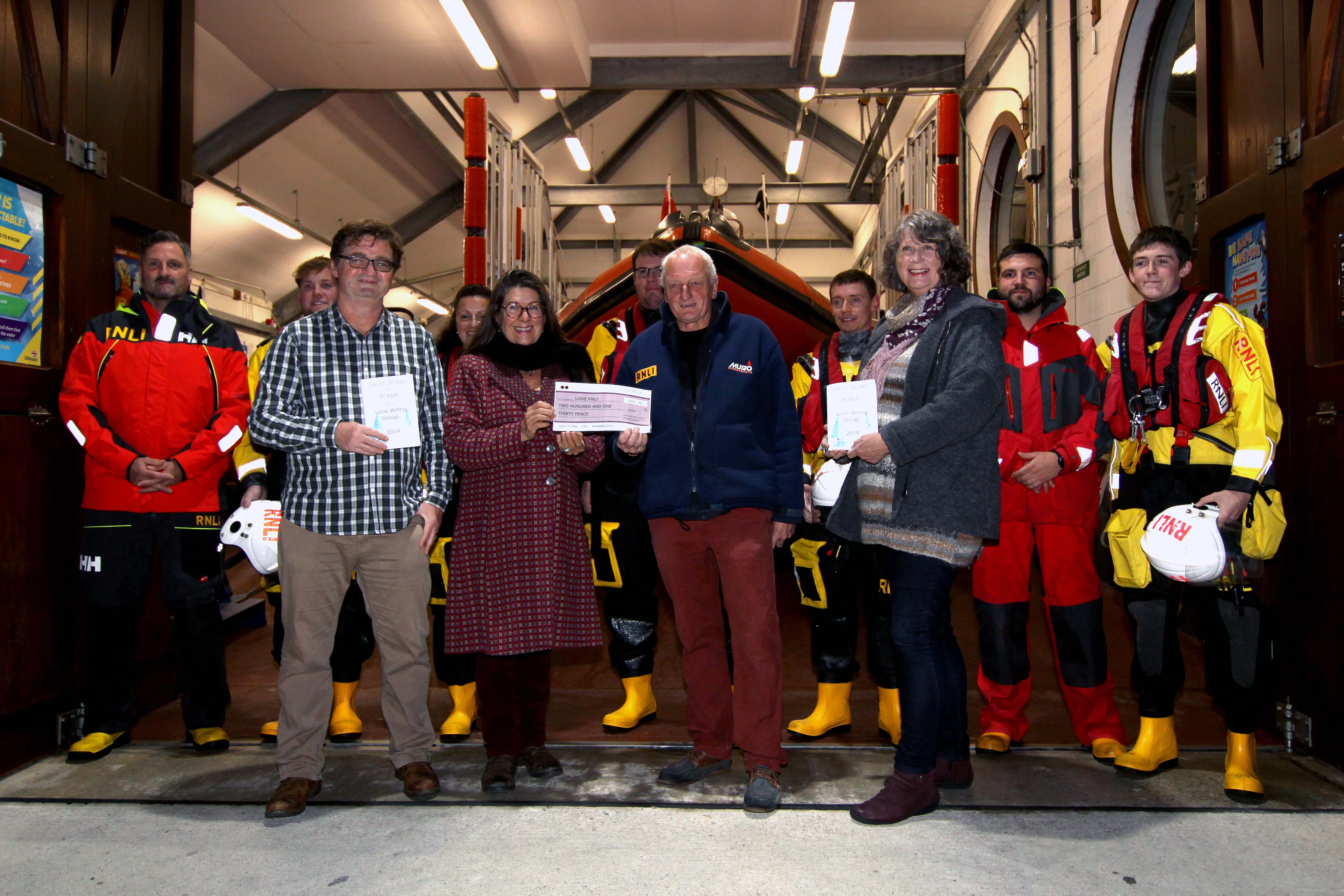 Cheque presentation by Jane Malcolm, Looe Writers Group to Dave Haines Looe RNLI with Jim Rickard, Viv Bennett and Looe RNLI volunteers crew