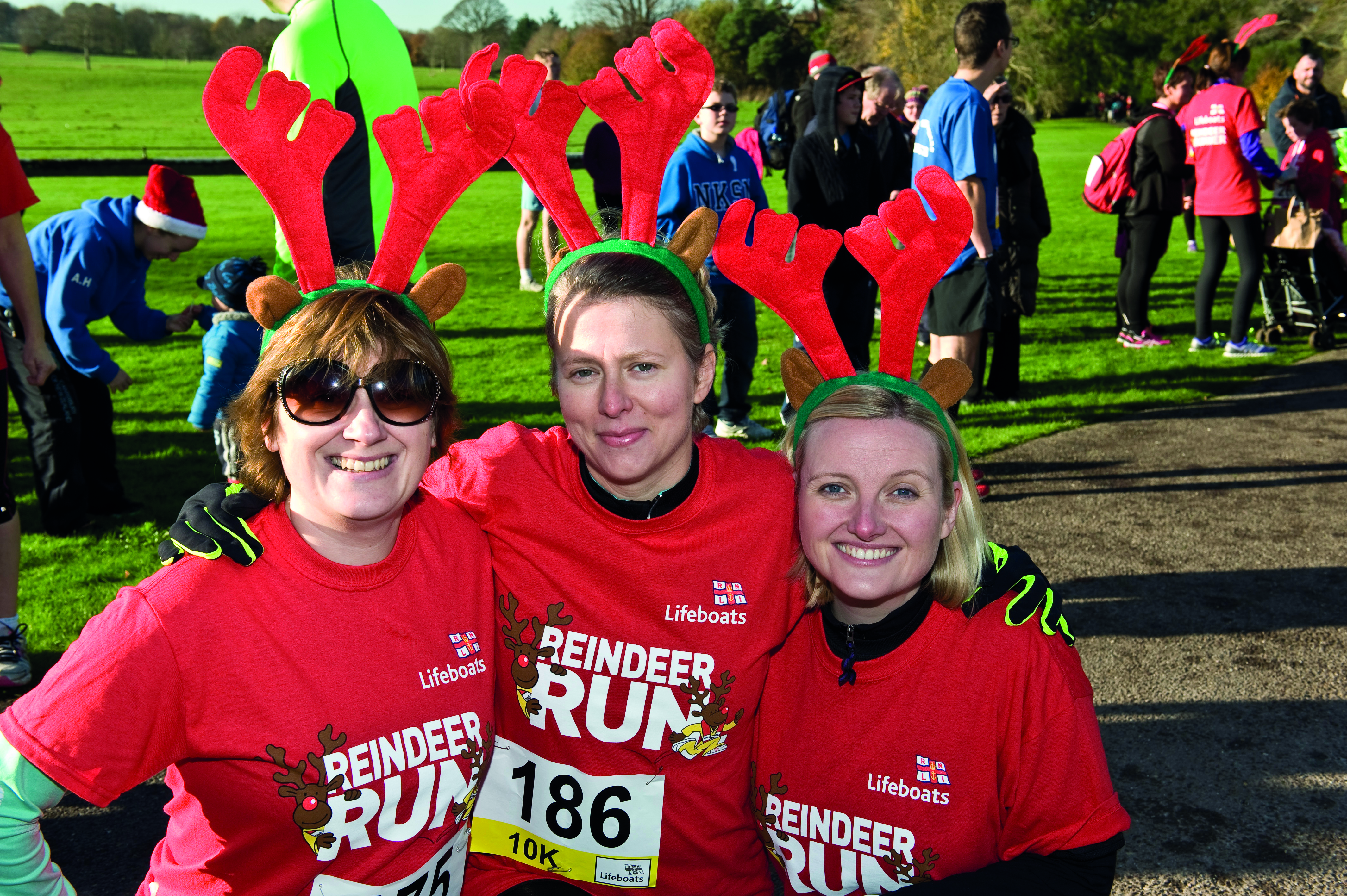 Photo of three participants in antlers from a previous Reindeer Run event.