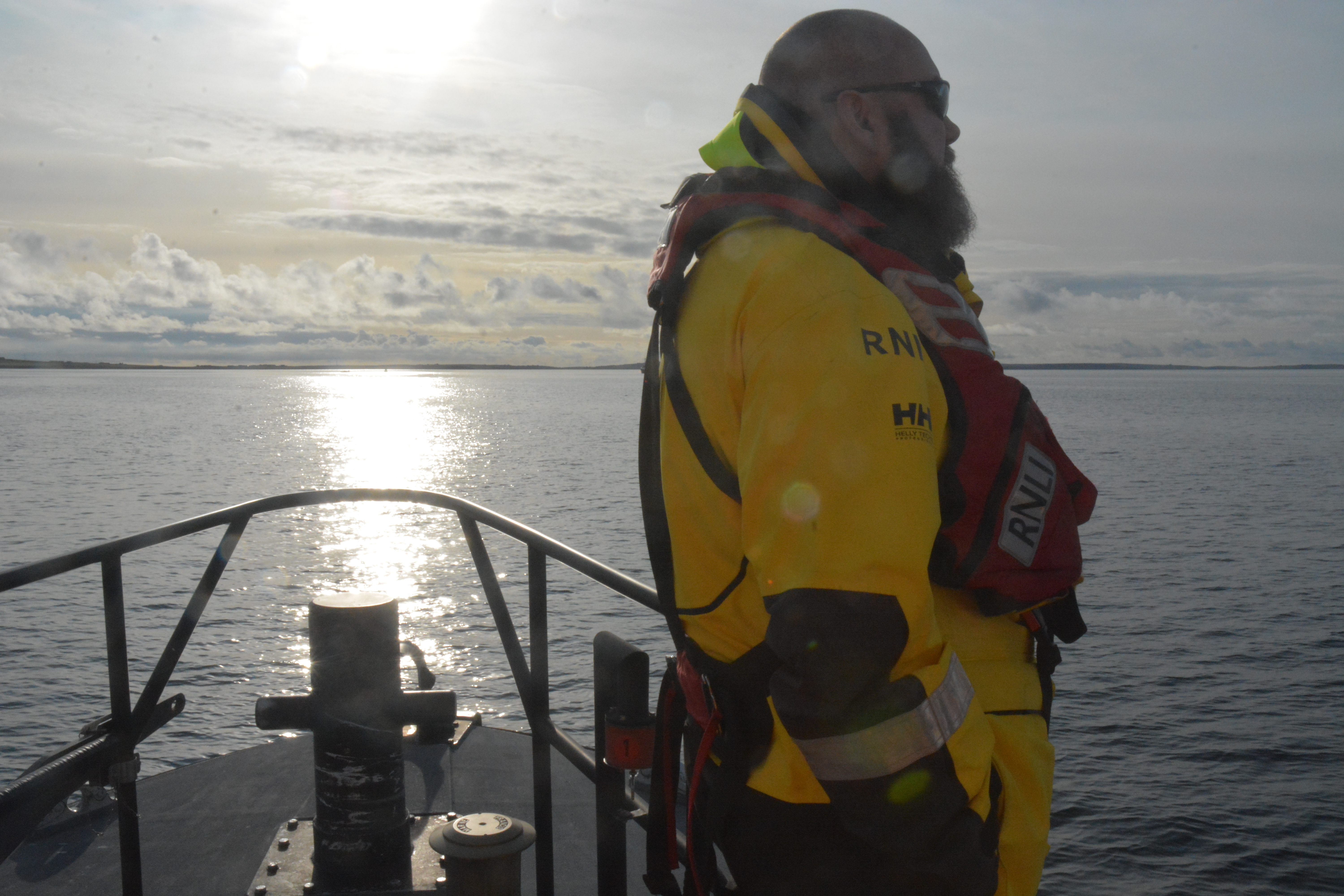 Solitary lifeboat crew member standing quietly at wreck site