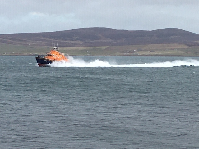 Lifeboat shown at full speed with Orkney hills in the background