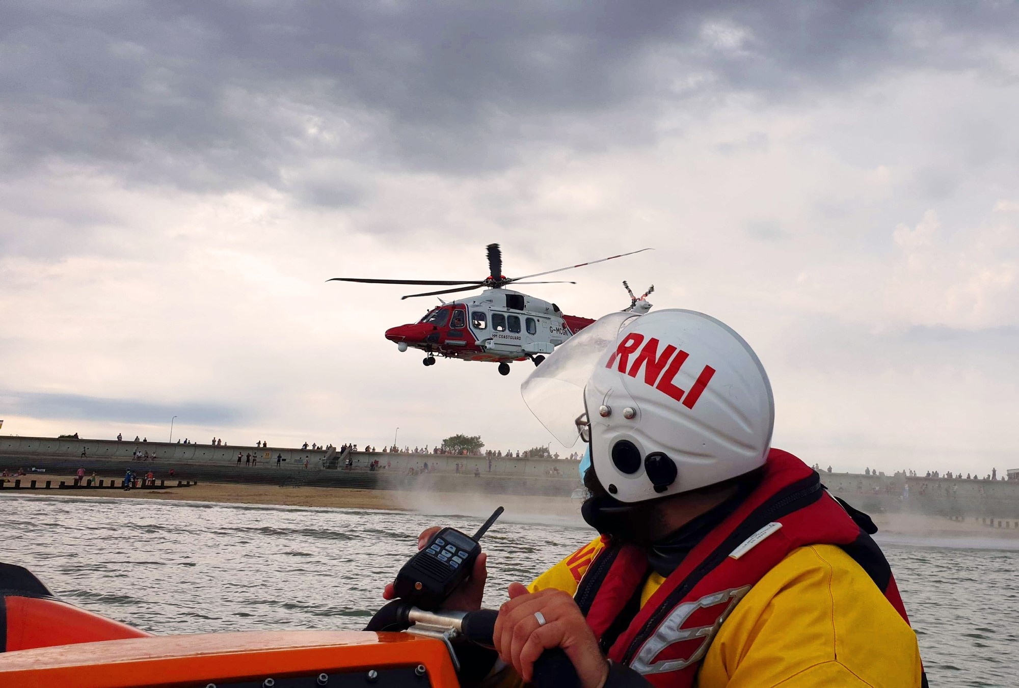 Photo showing crew member on board the RNLI lifeboat and HM Coastguard helicopter taking off from the beach.